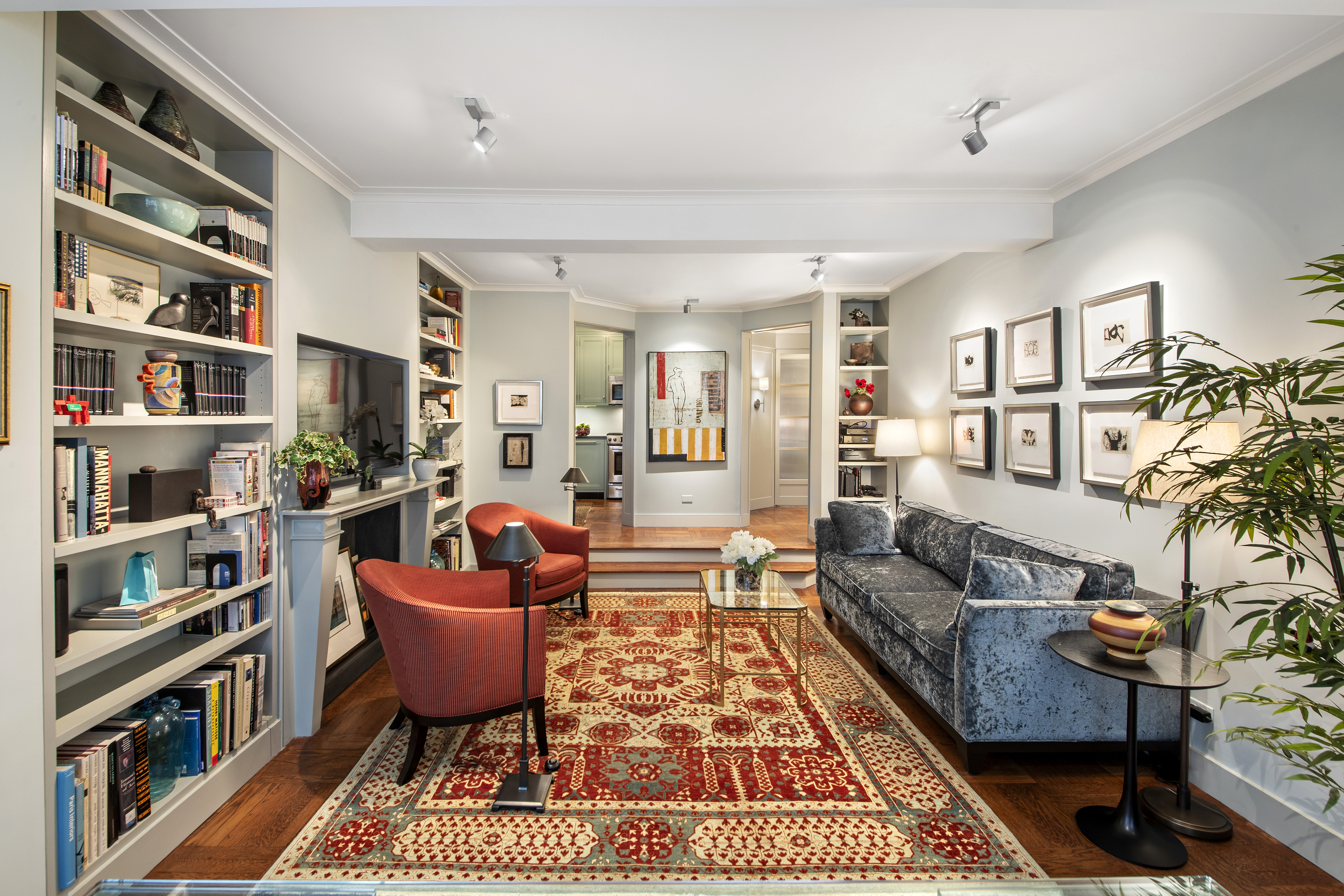 A sunken living room with a rug, built-in bookshelves, a planter, and a blue couch.