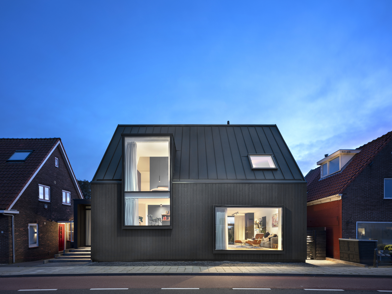 Black house with two large windows facing the street.
