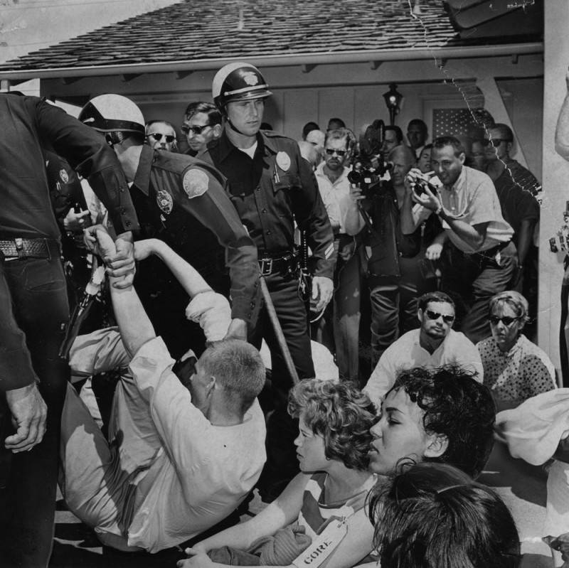 Black and white photo of police tussling with protestors. One officer is pulling a young man up by his arms.