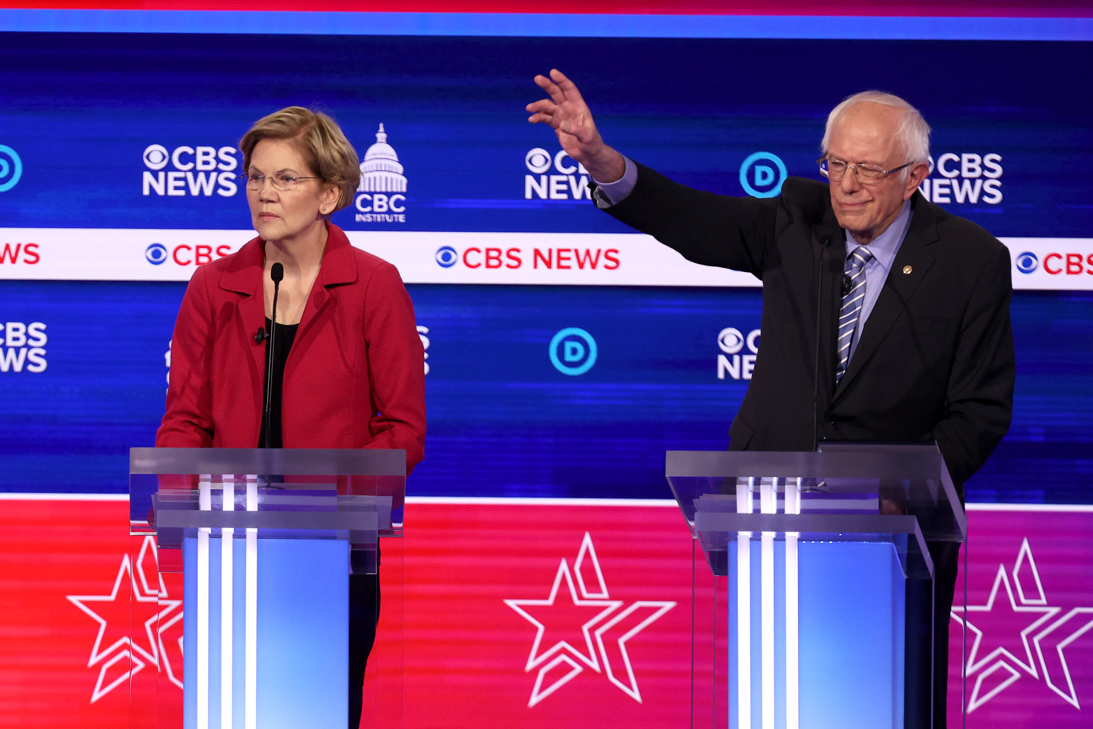 Senators Elizabeth Warren and Bernie Sanders standing behind podiums on the debate stage.