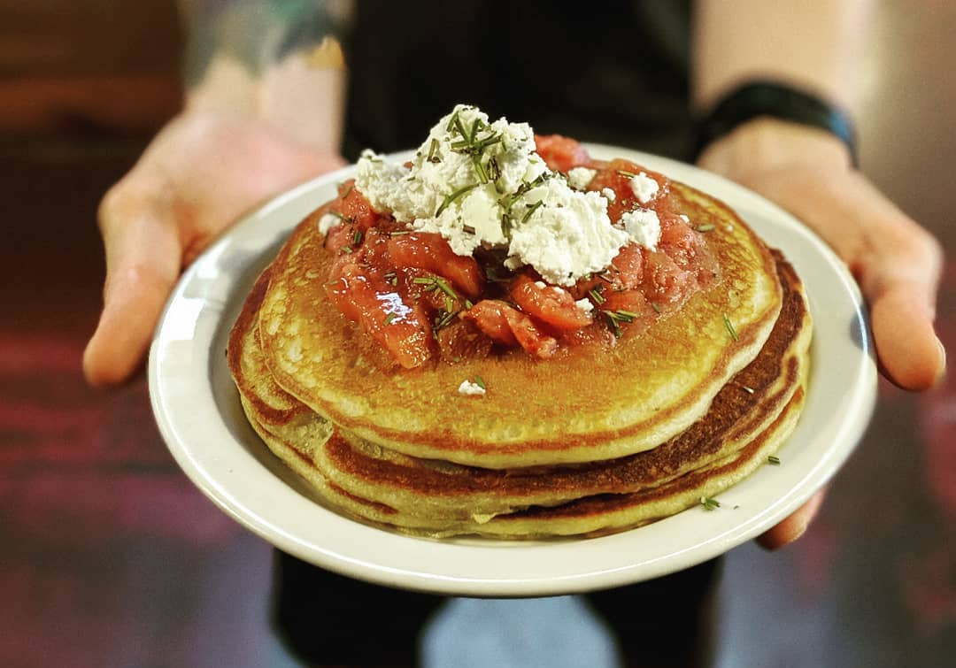 A pair of hands holds a plate of savory pancakes.