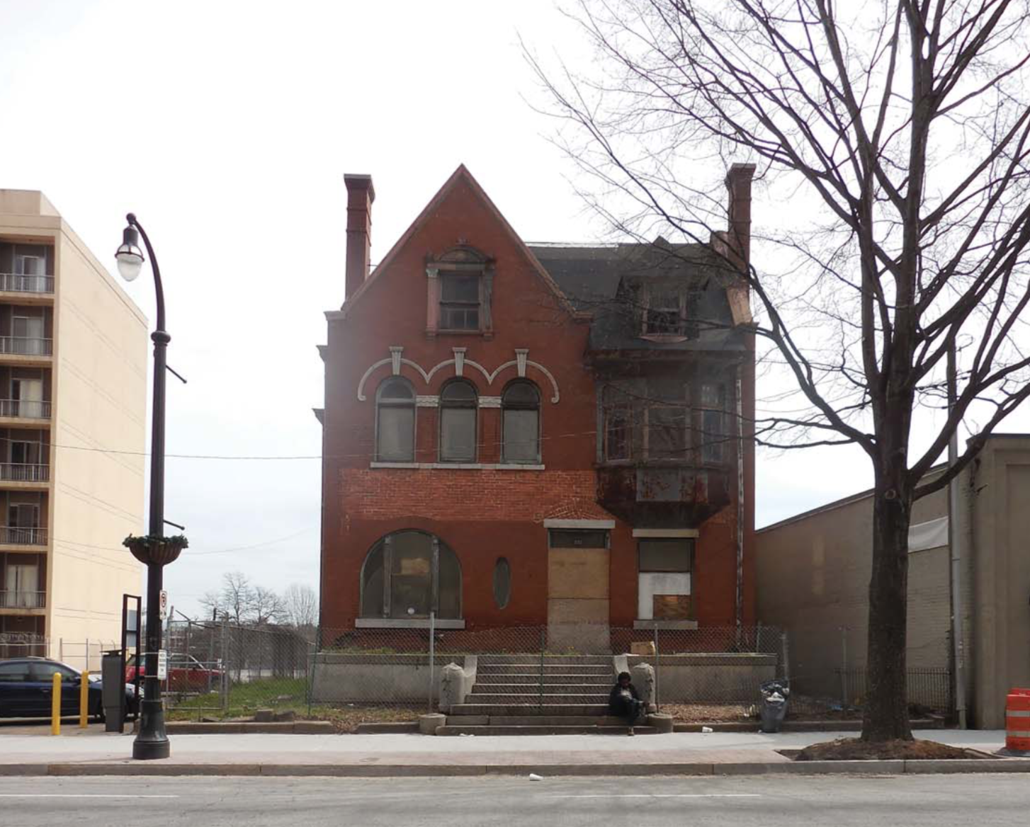 Two-story Victorian mansion in a rundown state.