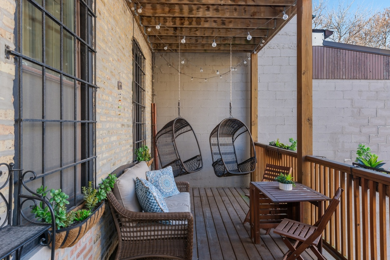 A back deck with window boxes. hanging chairs, a couch, and a wooden bistro table.