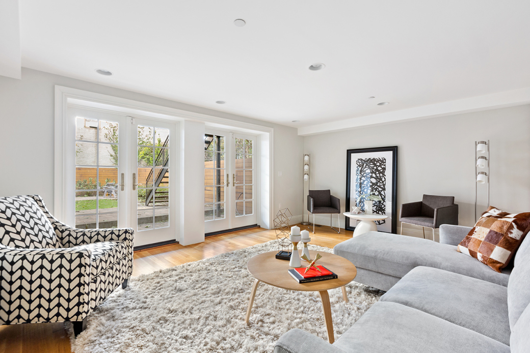 A living area with a beige rug, hardwood floors, light grey walls, a couch, several chairs, and French doors that lead to a garden.