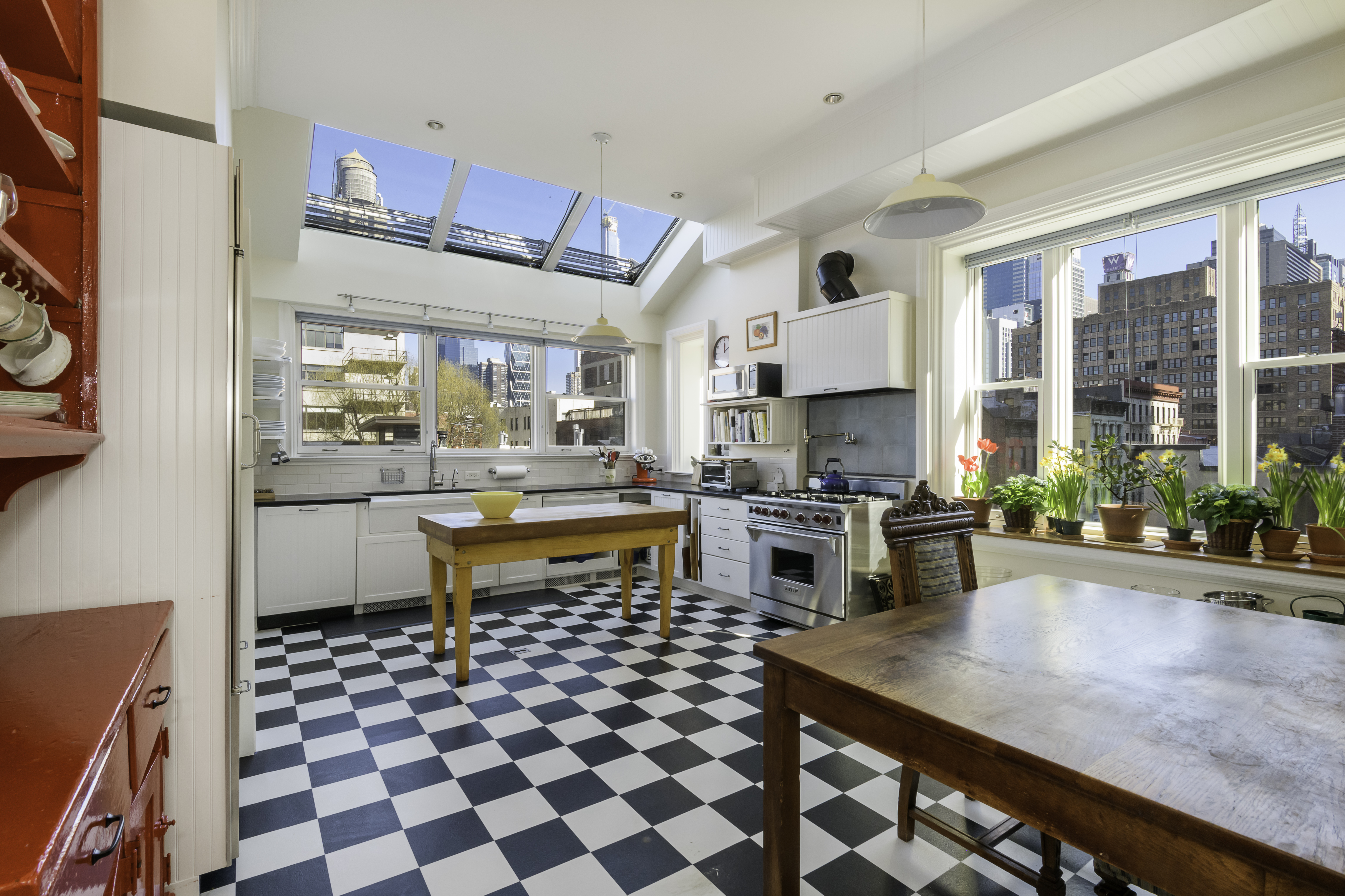 A large and bright kitchen features a black and white check floor, white cabinets, a huge skylight, and many windows overlooking the rooftops of Hell's Kitchen.
