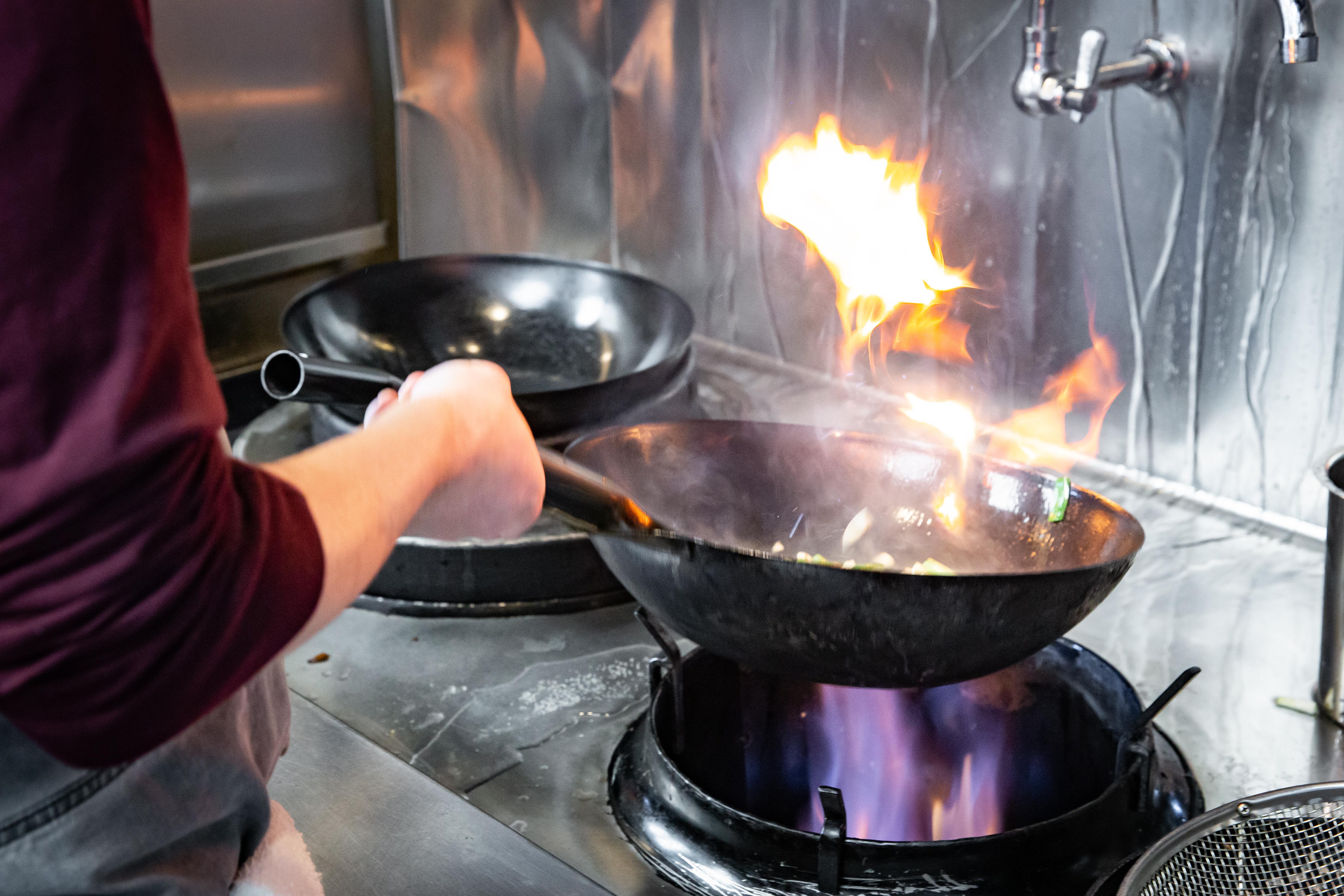 A flaming wok being flung.