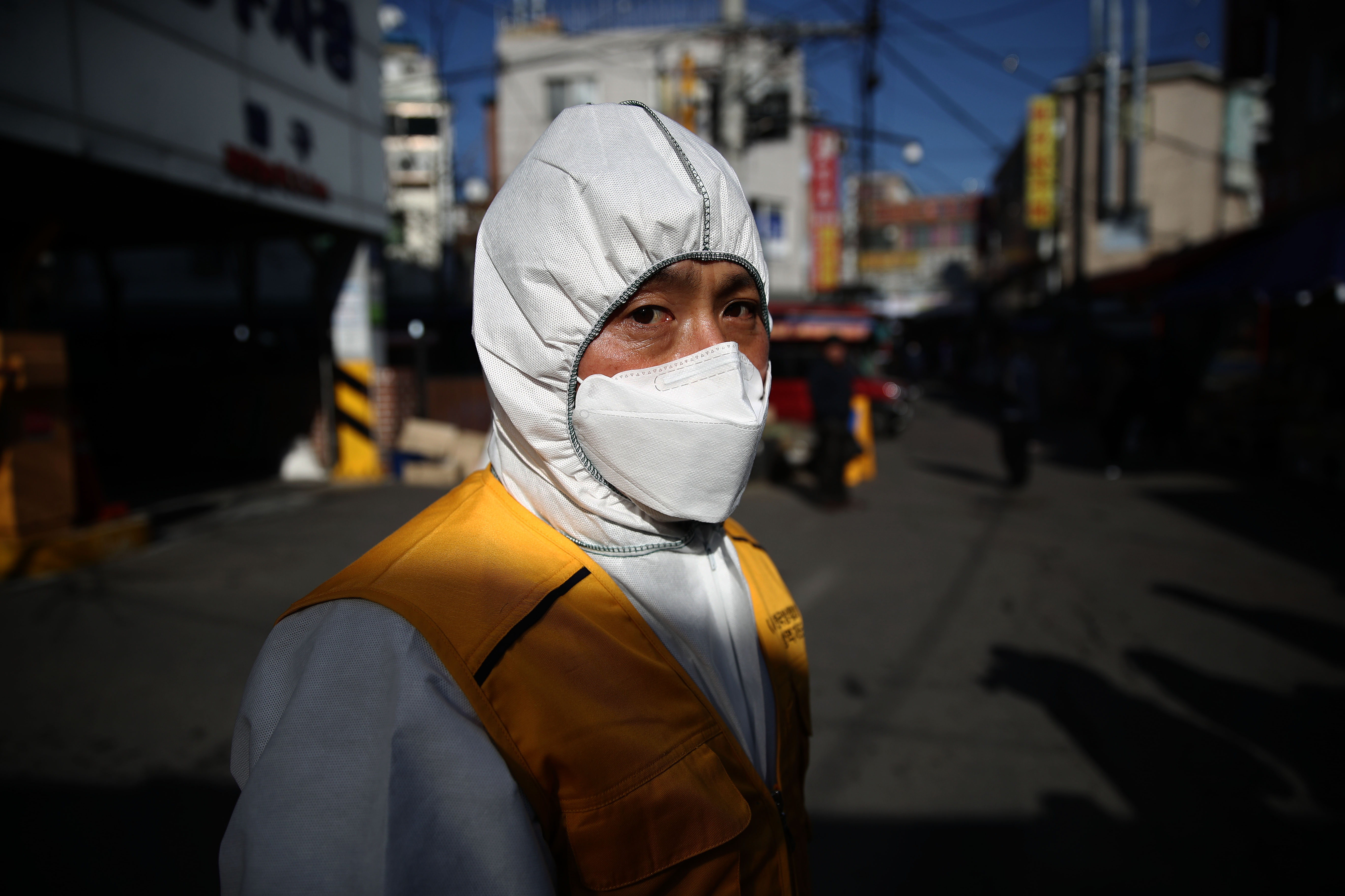 A man wearing a medical mask stands in a street.
