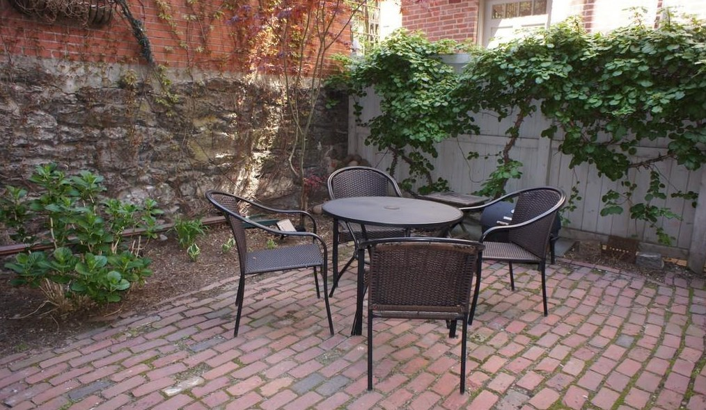 A brick patio with a table and four chairs, and there are vines growing on a nearby fence.