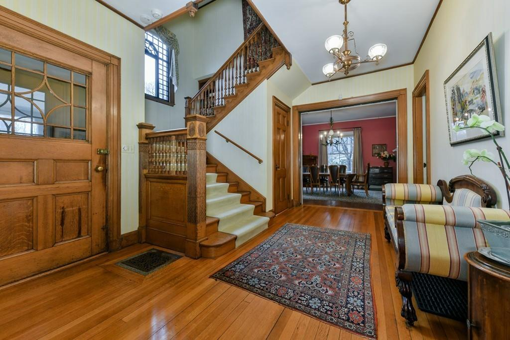 An airy entry foyer with a staircase with a landing.