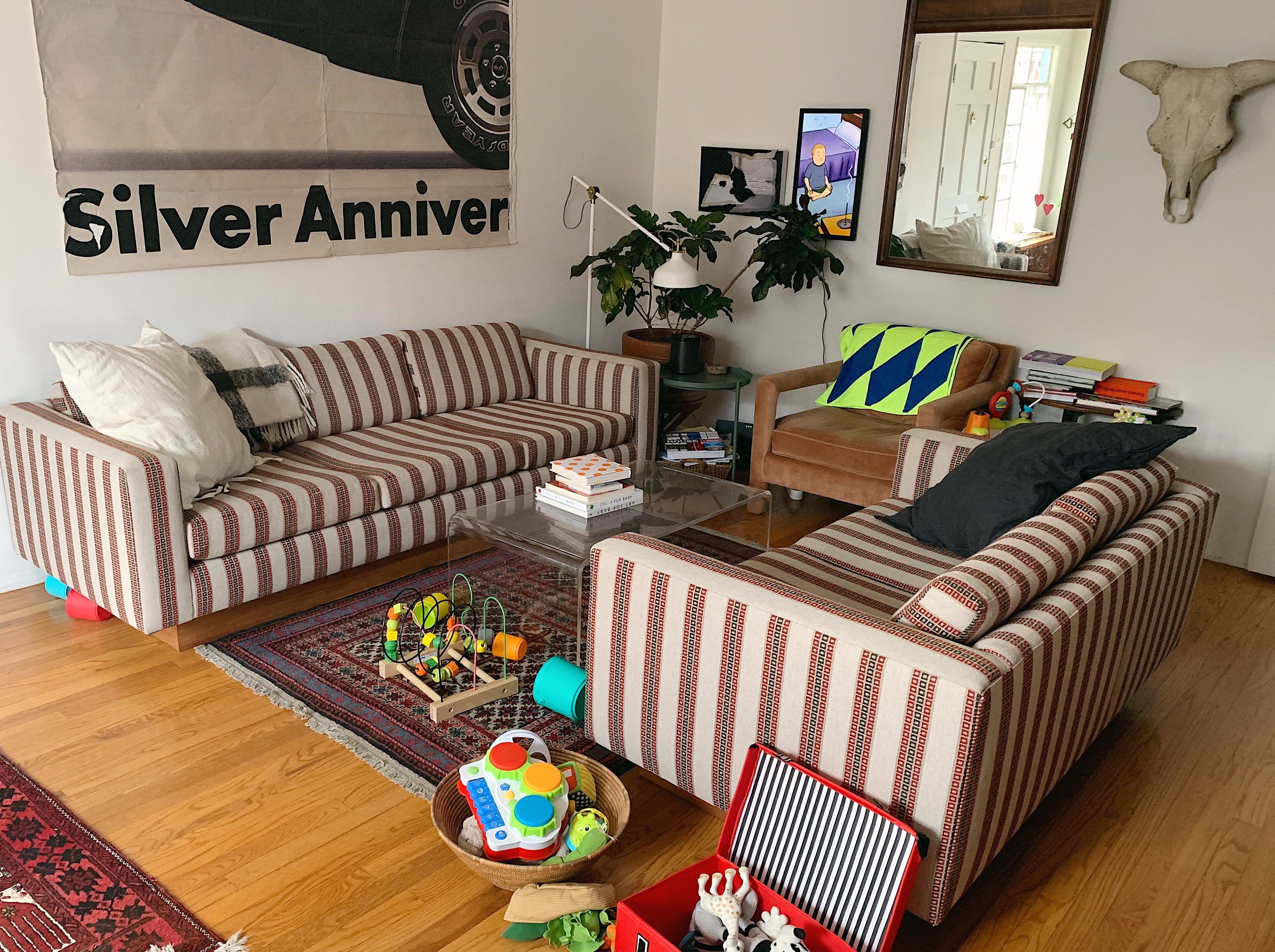 Two sofas in a striped red, green, and tan pattern face each other, with a coffee table in the middle, in a large room. A large poster hangs on the wall along with a mirror, two picture frames, and a steer skull. Baby toys are on the floor, near the rug.