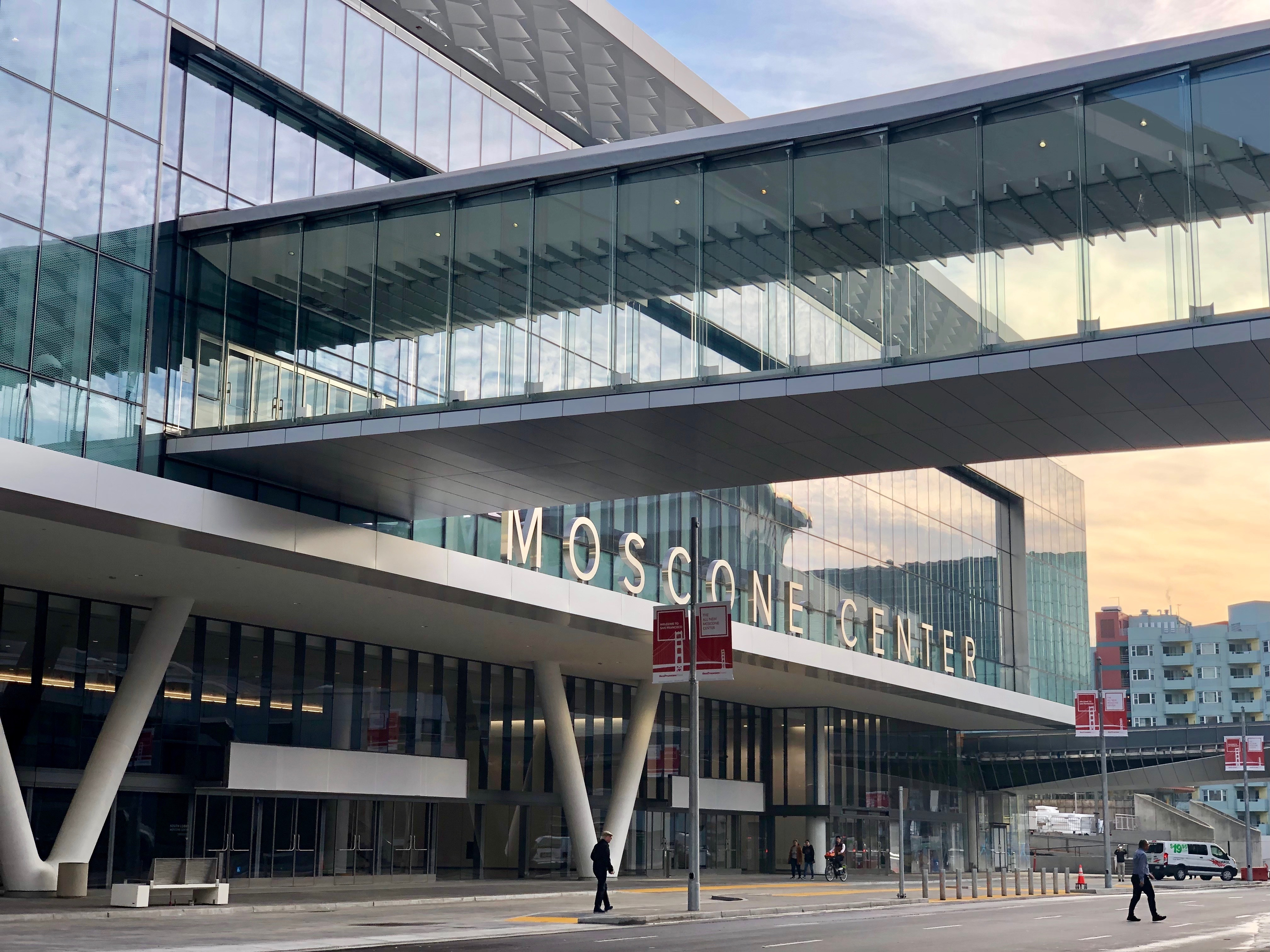 """A glass-enclosed pedestrian bridge leading into the second story of a broad building with lettering out front reading """"Moscone Center."""""""