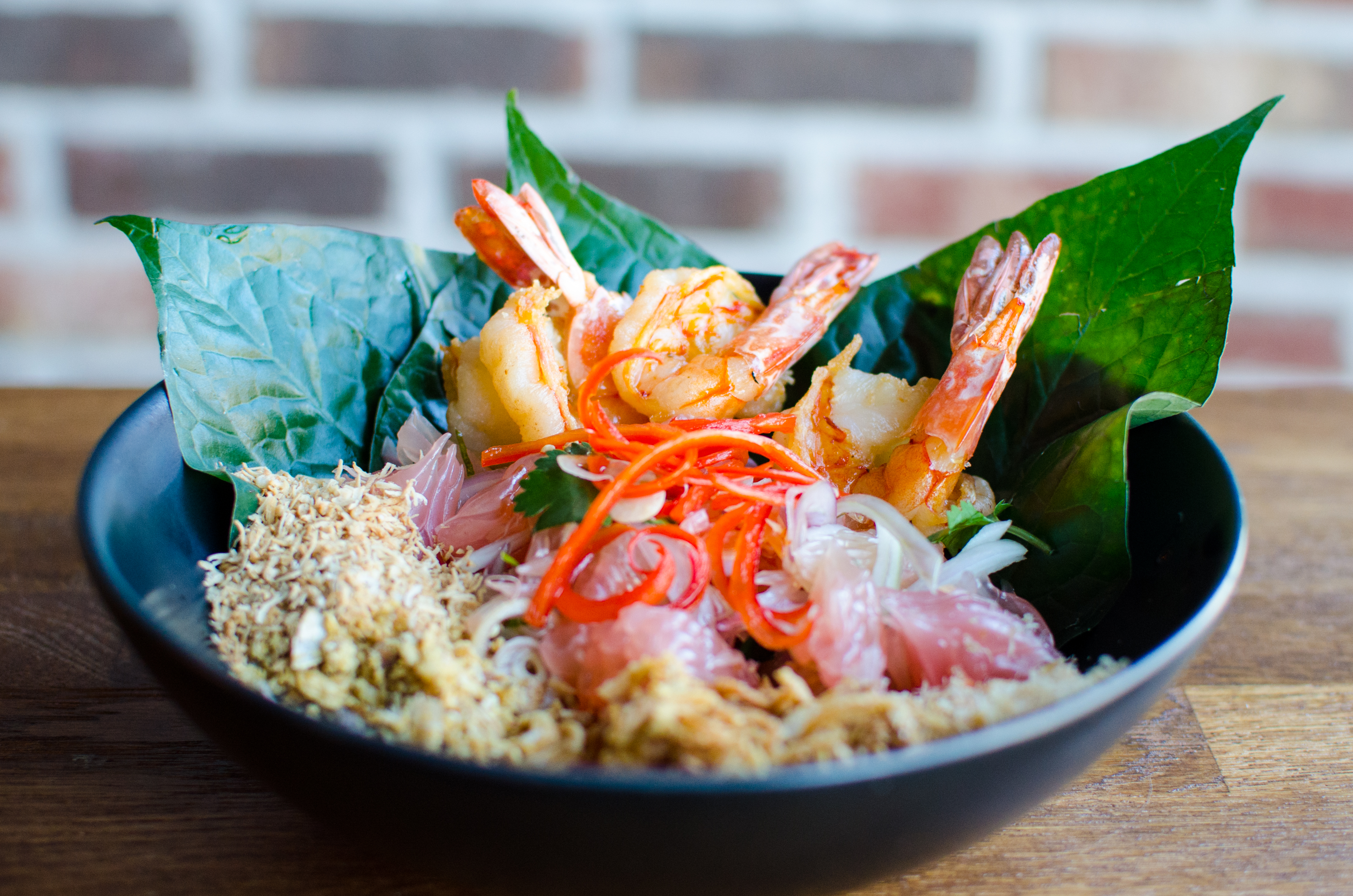 A Thai pomelo salad with shrimp, betel leaves, thinly sliced red chile, and a variety of crispy condiments sits in a black bowl on a wooden table in front of a brick background
