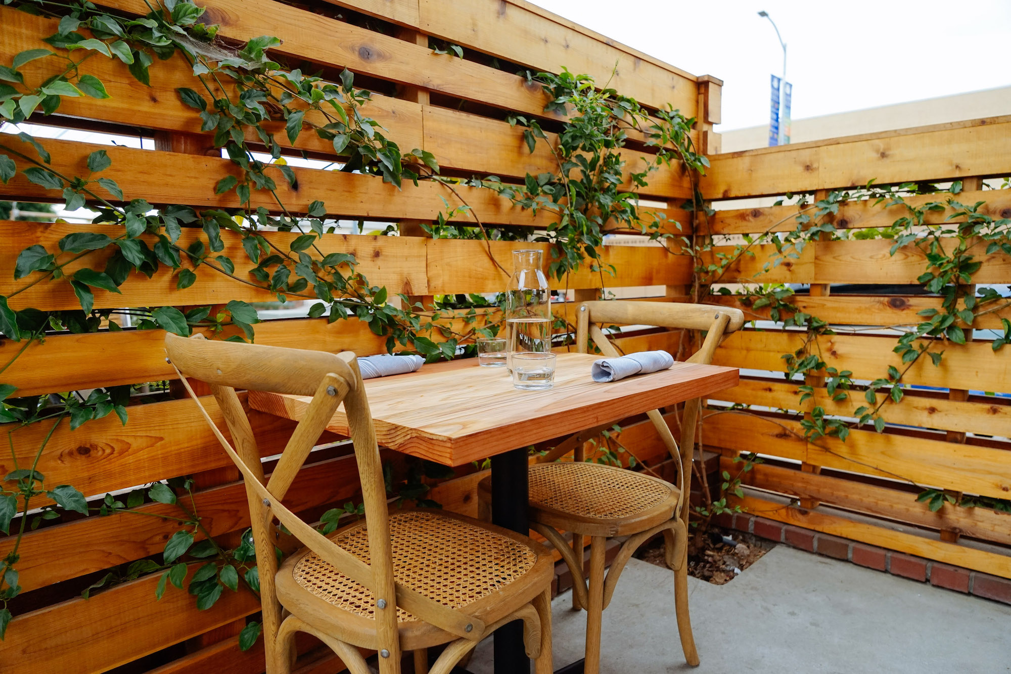 A wooden table and chairs sit on a leafy restaurant patio.