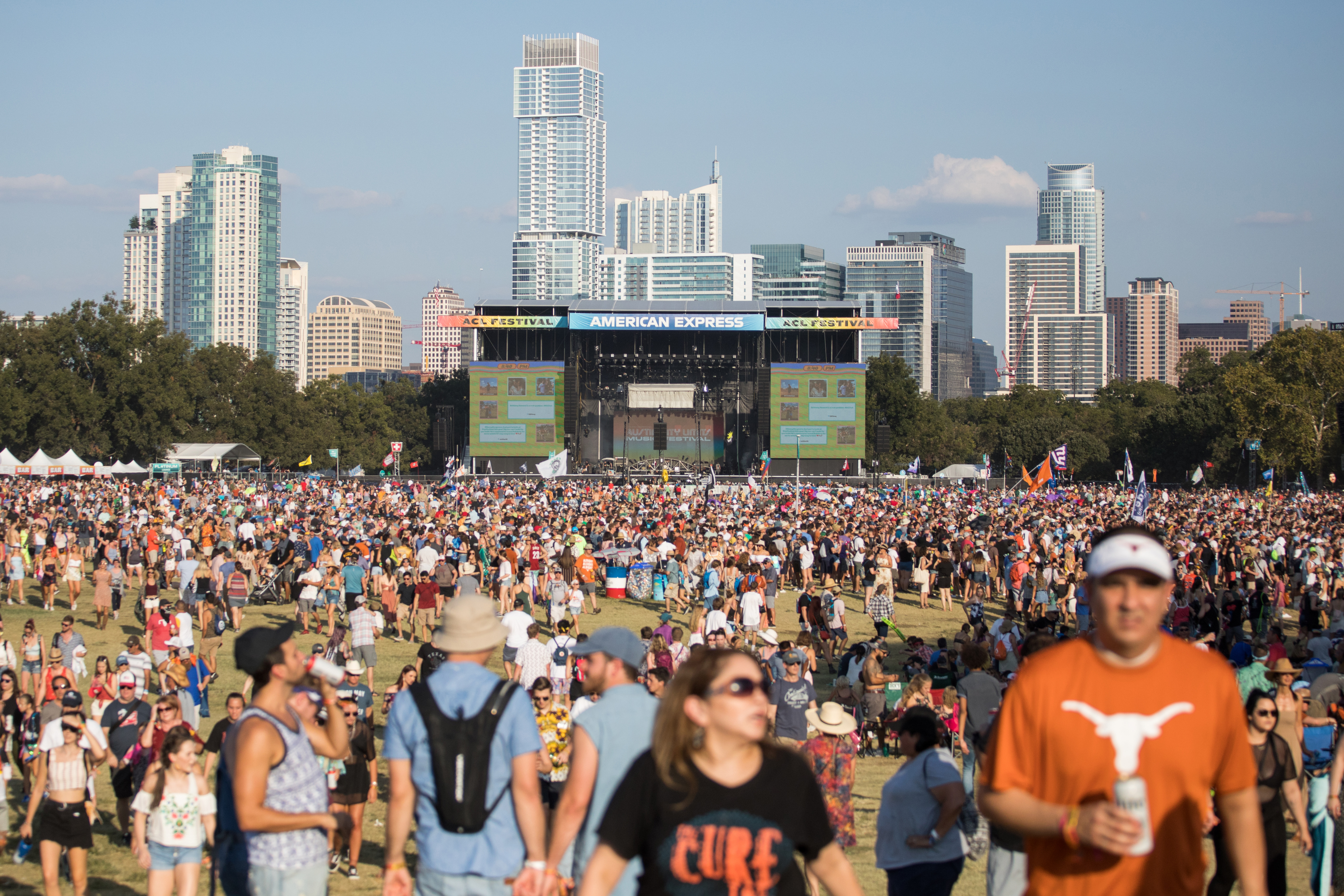 Thousands of concert-goers fill a field in front of an outdoor stage.