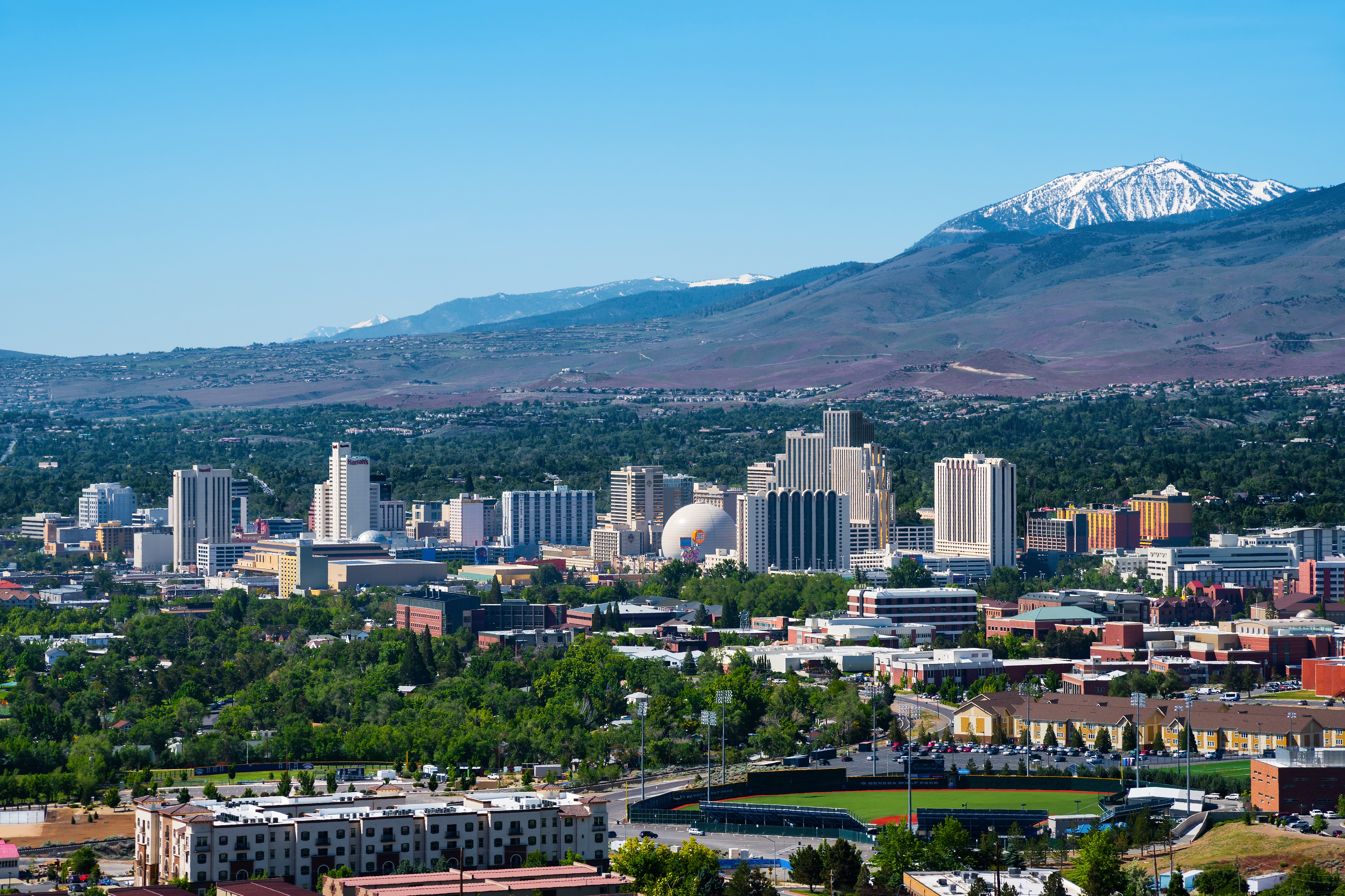 Reno's colorful skyline with a cluster of large casino buildings at the center, with a snowcapped mountains in the background.