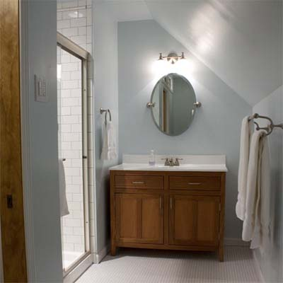 Bathroom with light and oval mirror above sink.