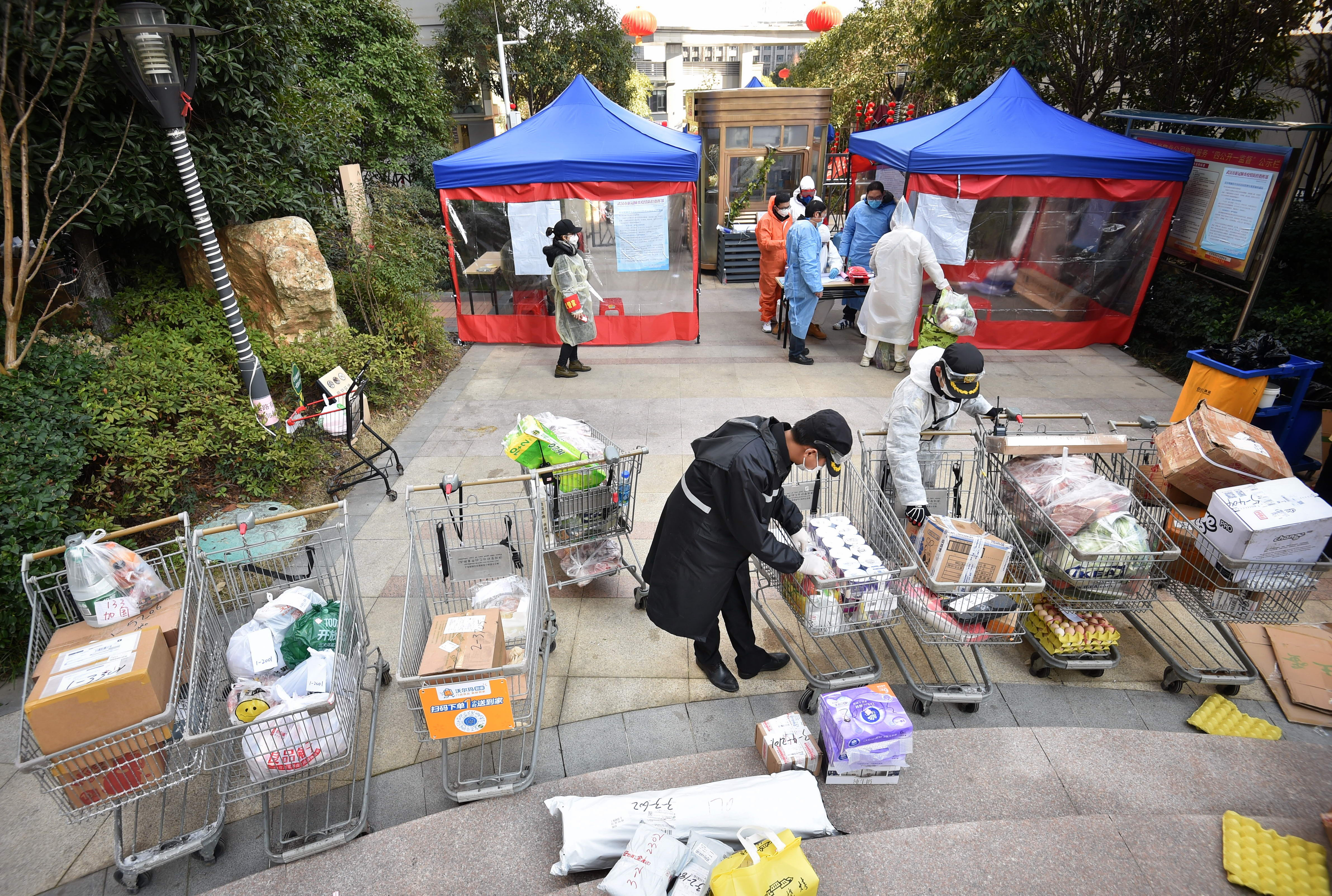 Workers wearing masks load food into carts to deliver them to an apartment complex in the background.