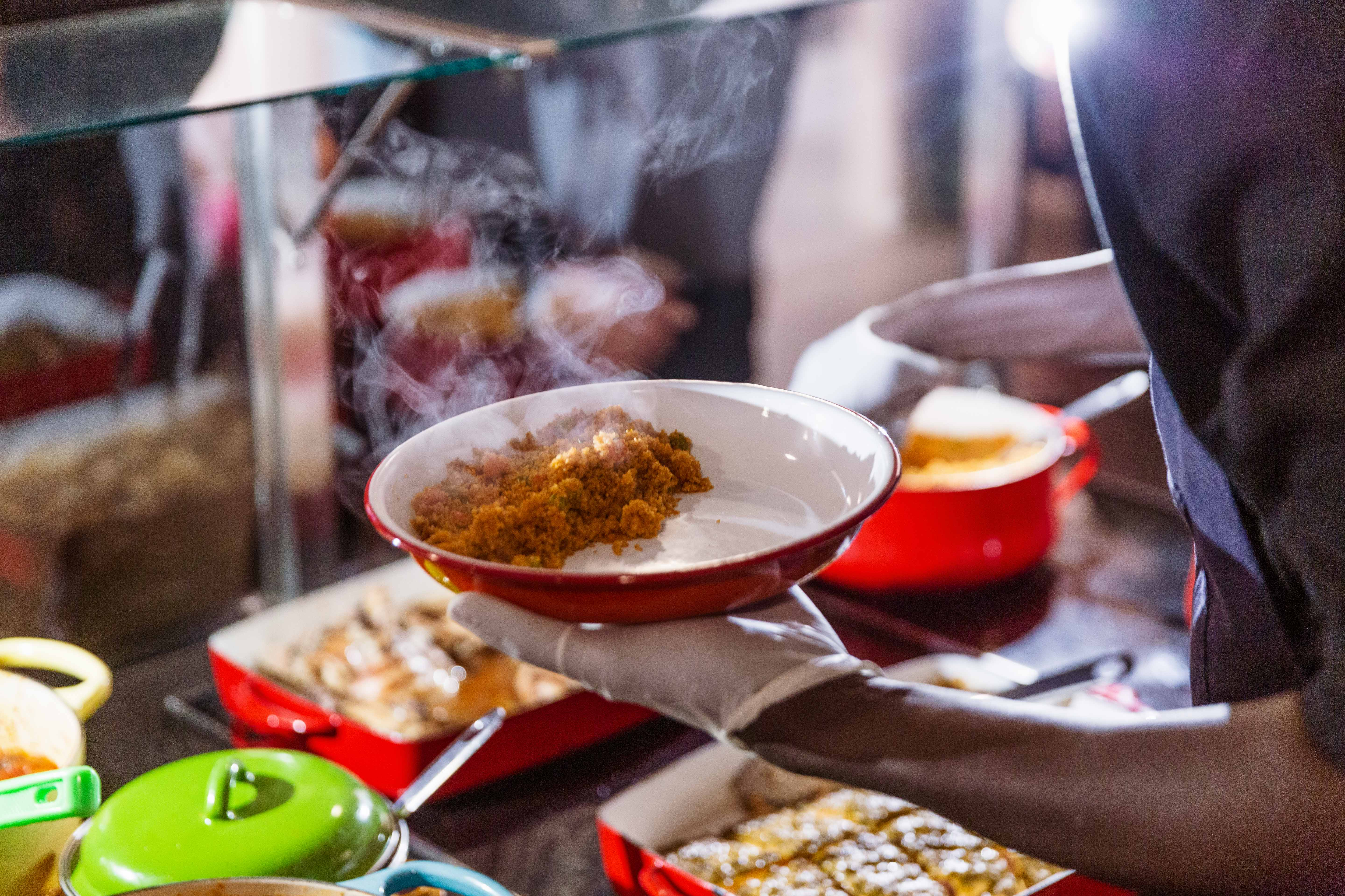 Steam rises over a plate of jollof fonio, which sits in a white plate at Teranga