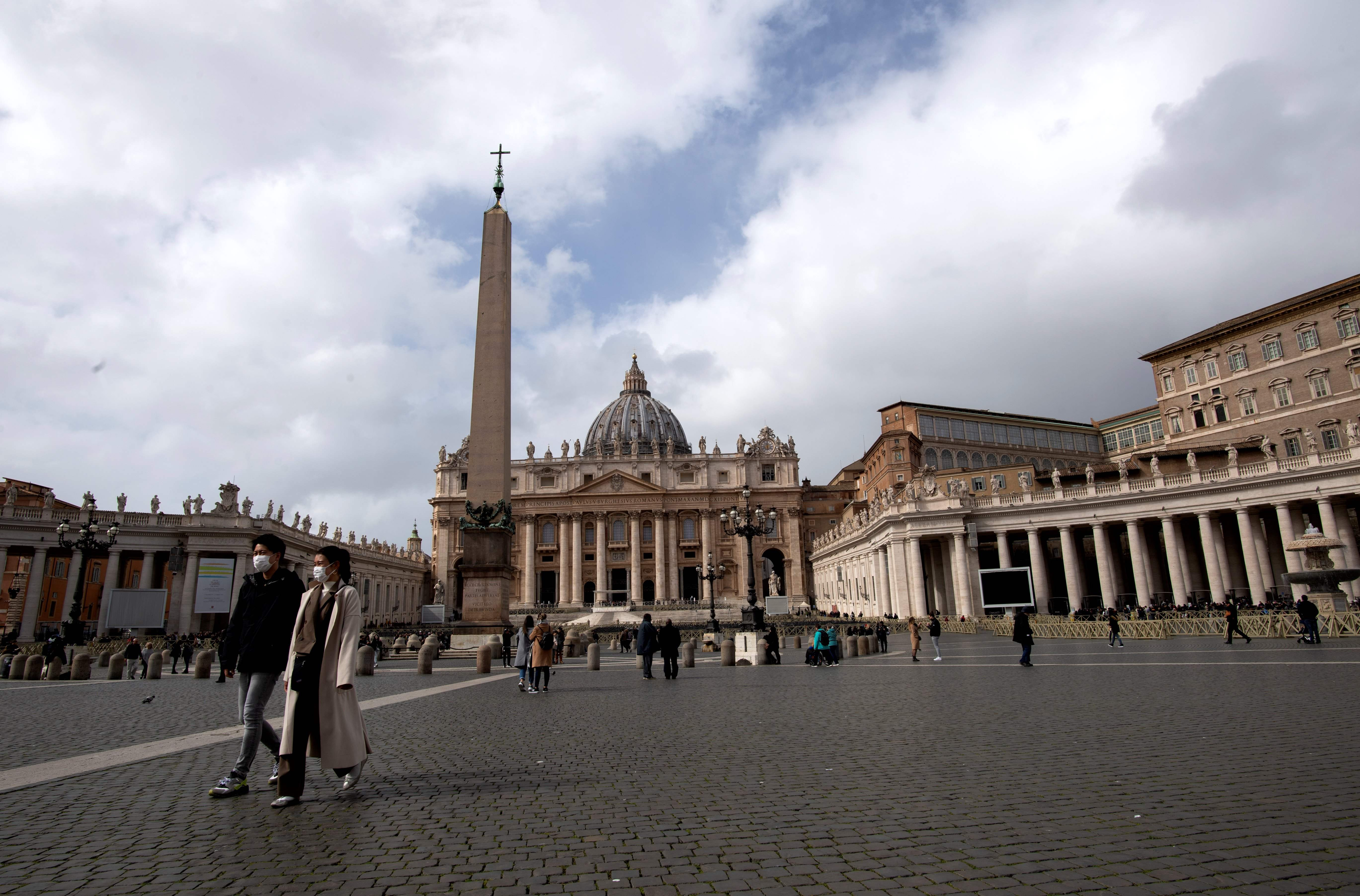 Tourists wearing a protective mask walk in St. Peter's Square at the Vatican in Rome on Tuesday.