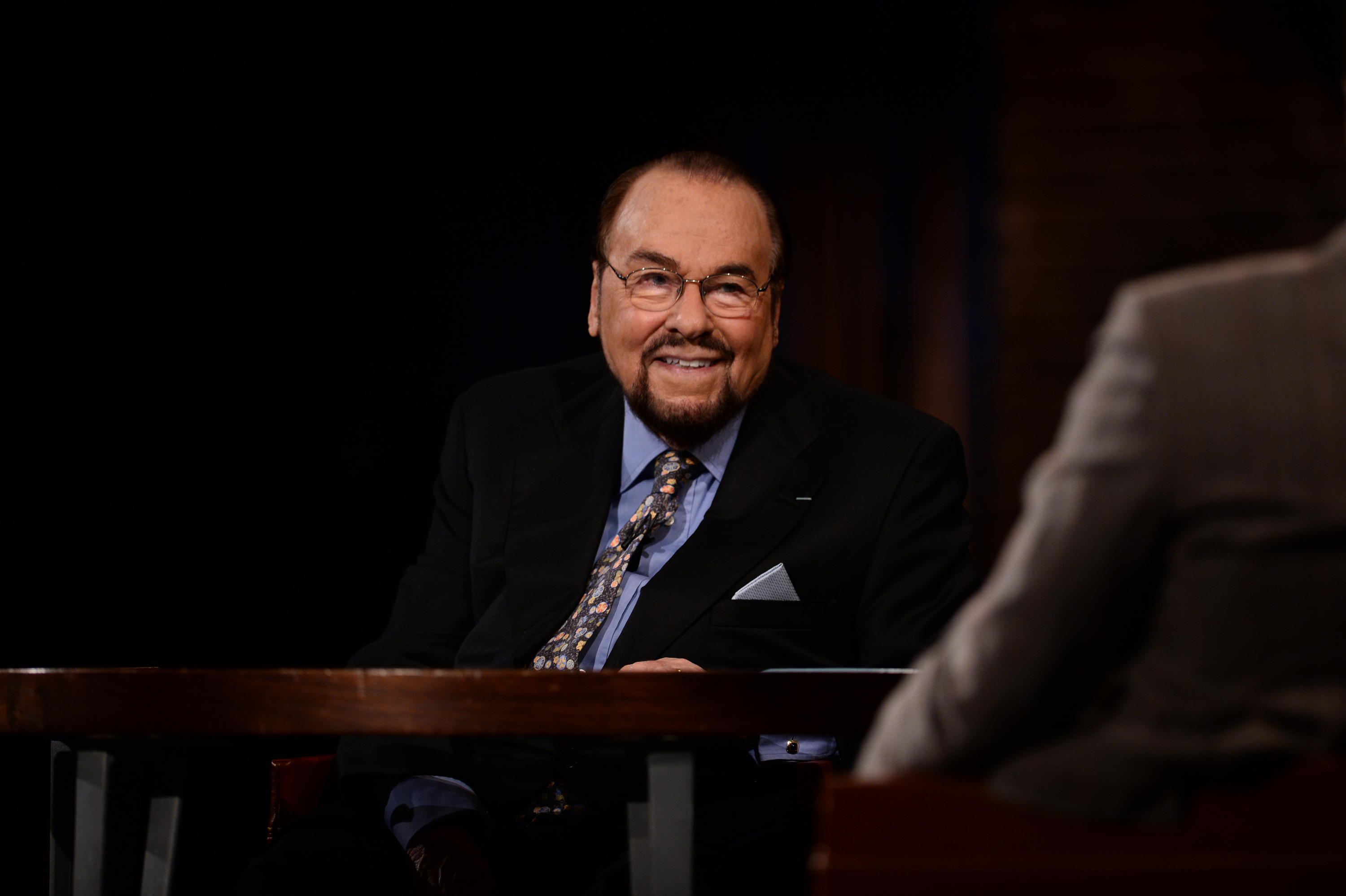 James Lipton sitting at a table smiling. He has a goatee, and is wearing a black suite and blue/pink patterned tie.
