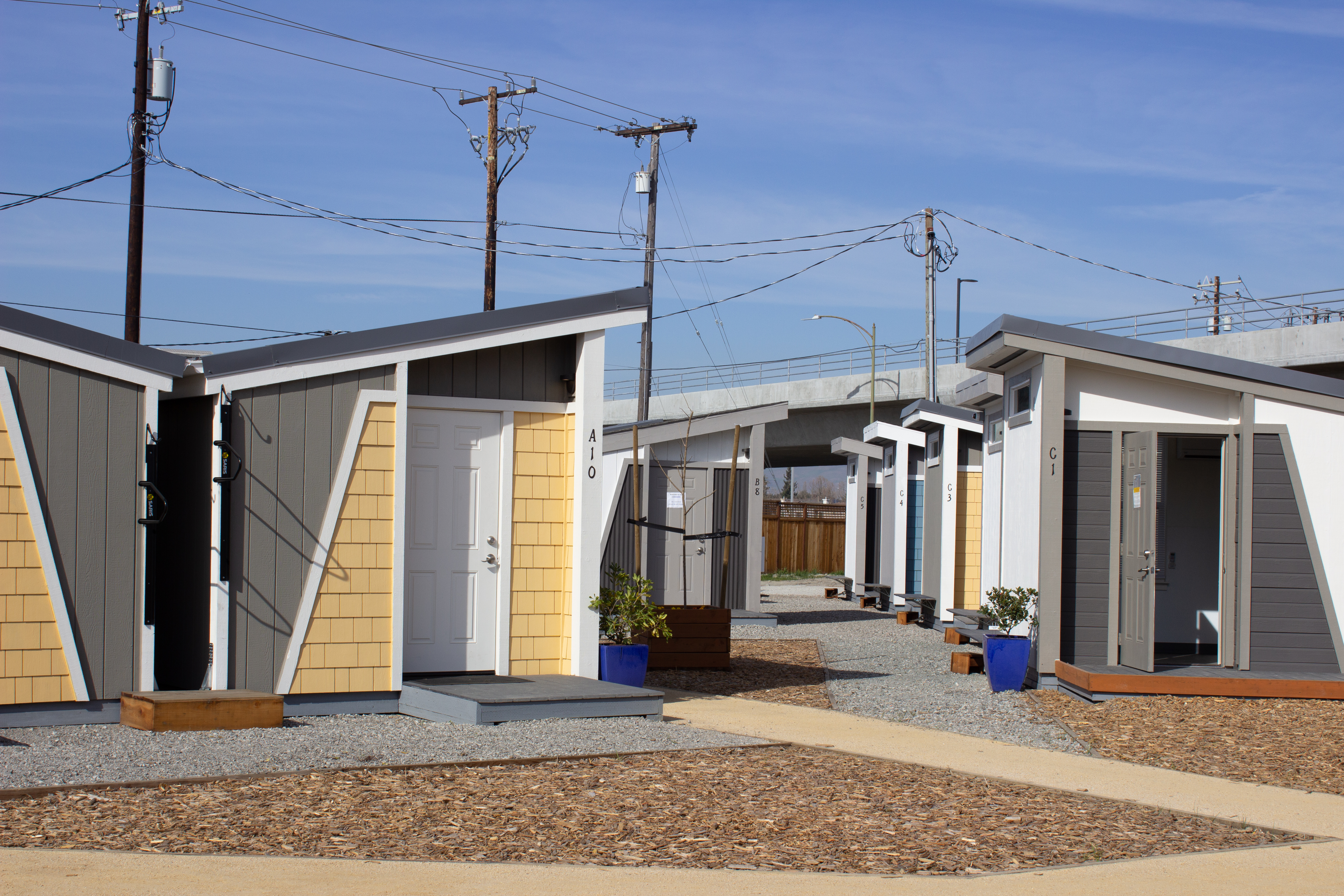 A series of small tiny homes with angled rooftops and yellow wood paneled facades.