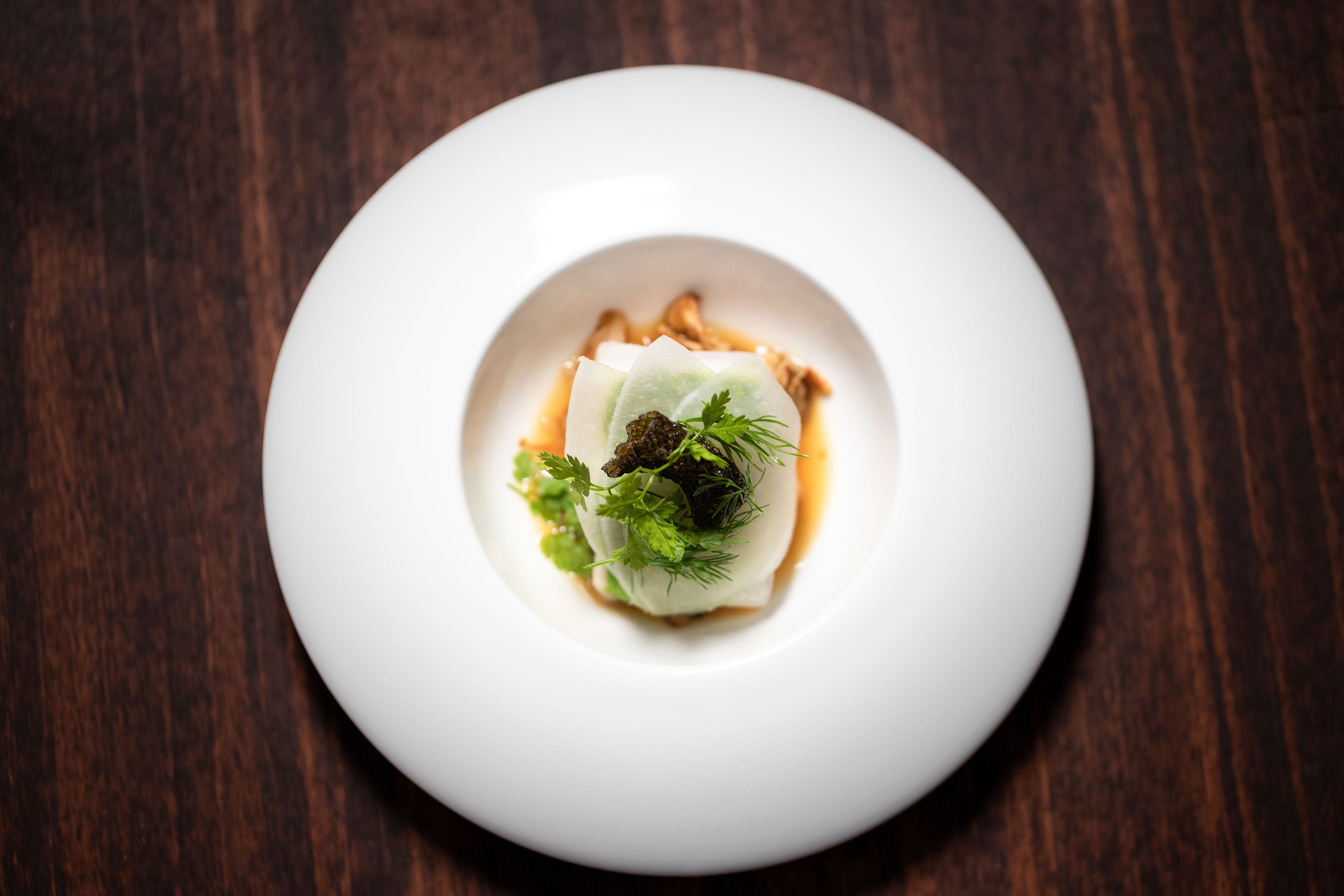 Top-down view of black cod with matsutake mushroom, turnups, and dill on a white plate.