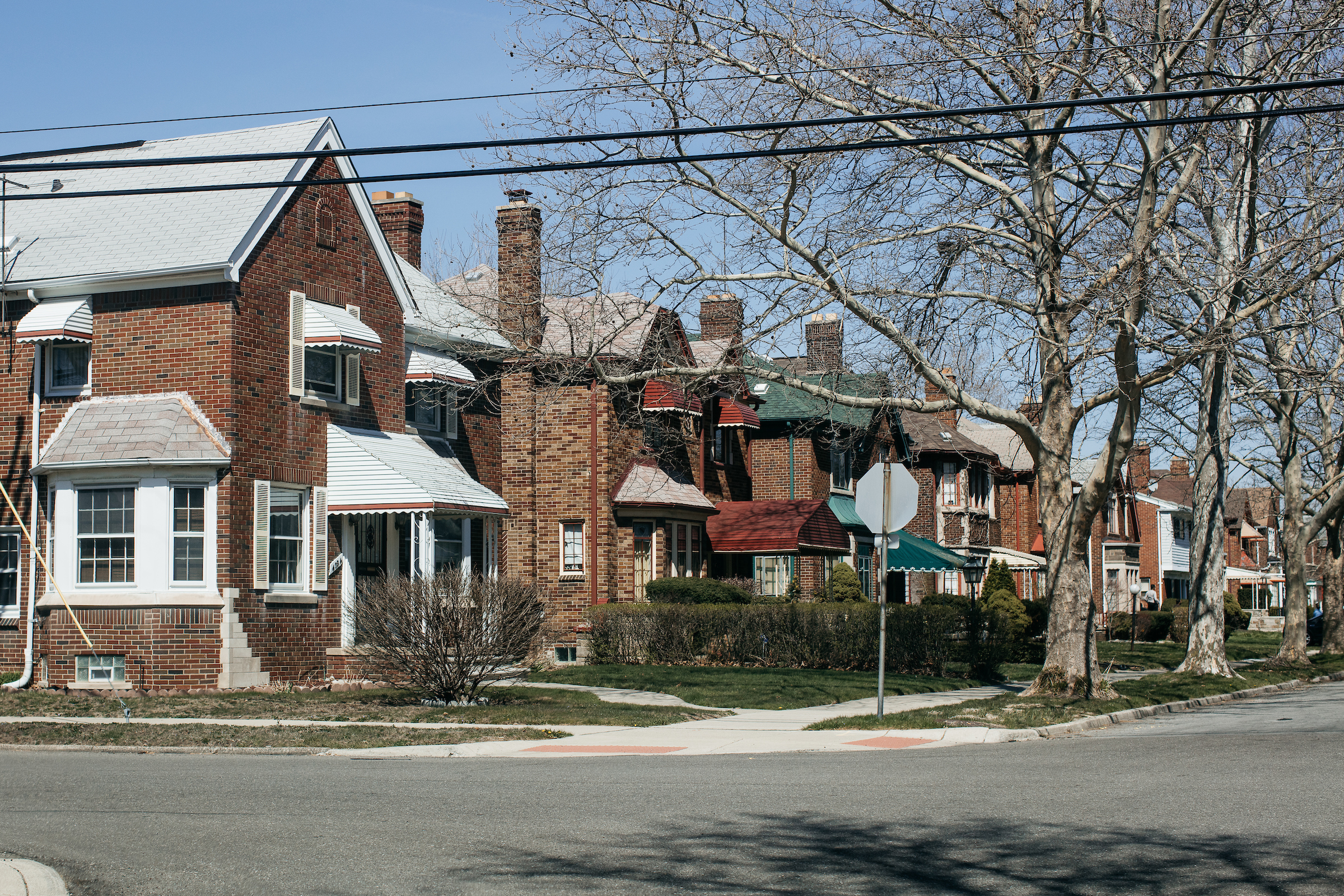 A street lined with two-story brick homes. Many of the windows have awnings over them.