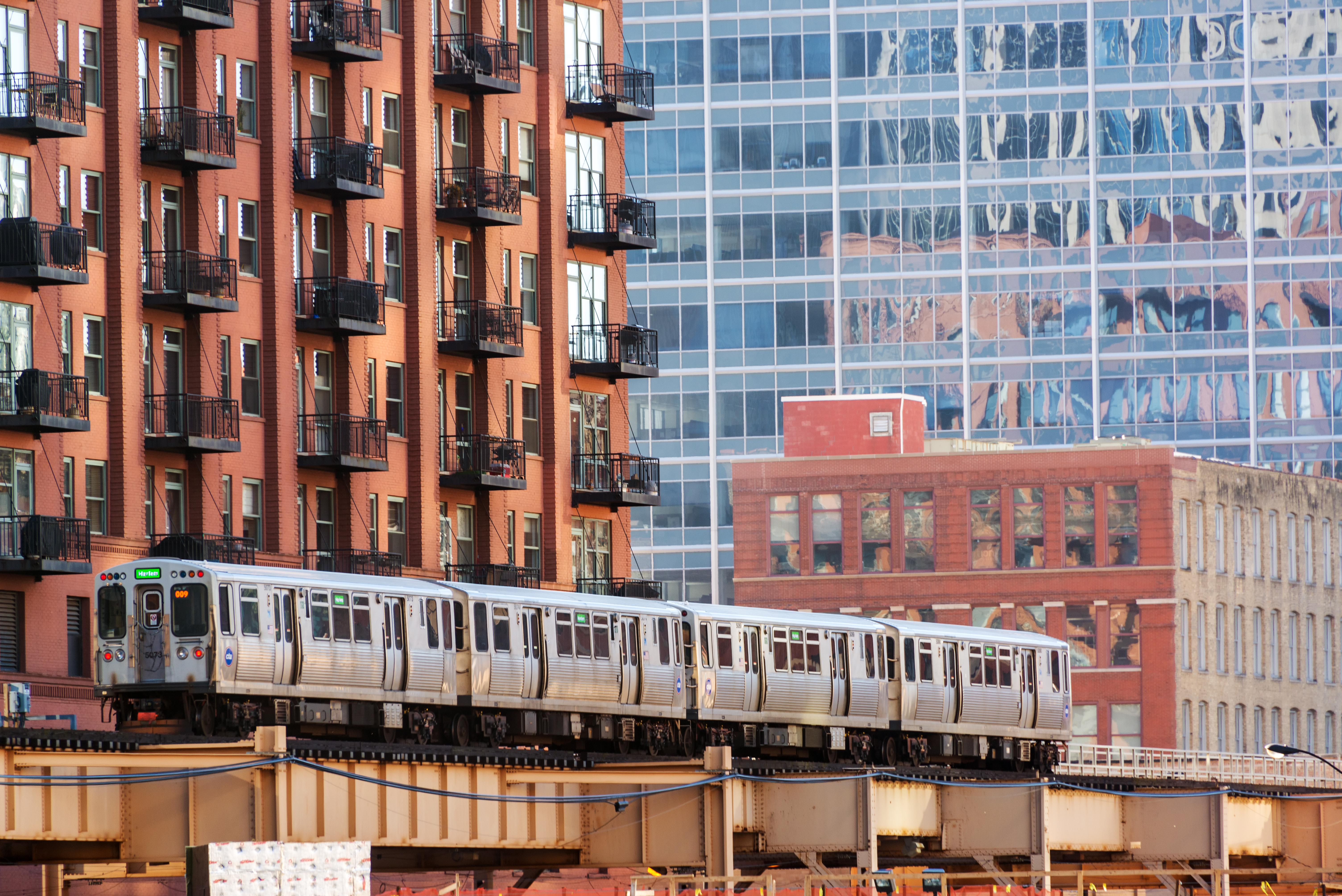 A silver train from the CTA crosses the tracks. There are brick buildings in the background of the downtown scene.