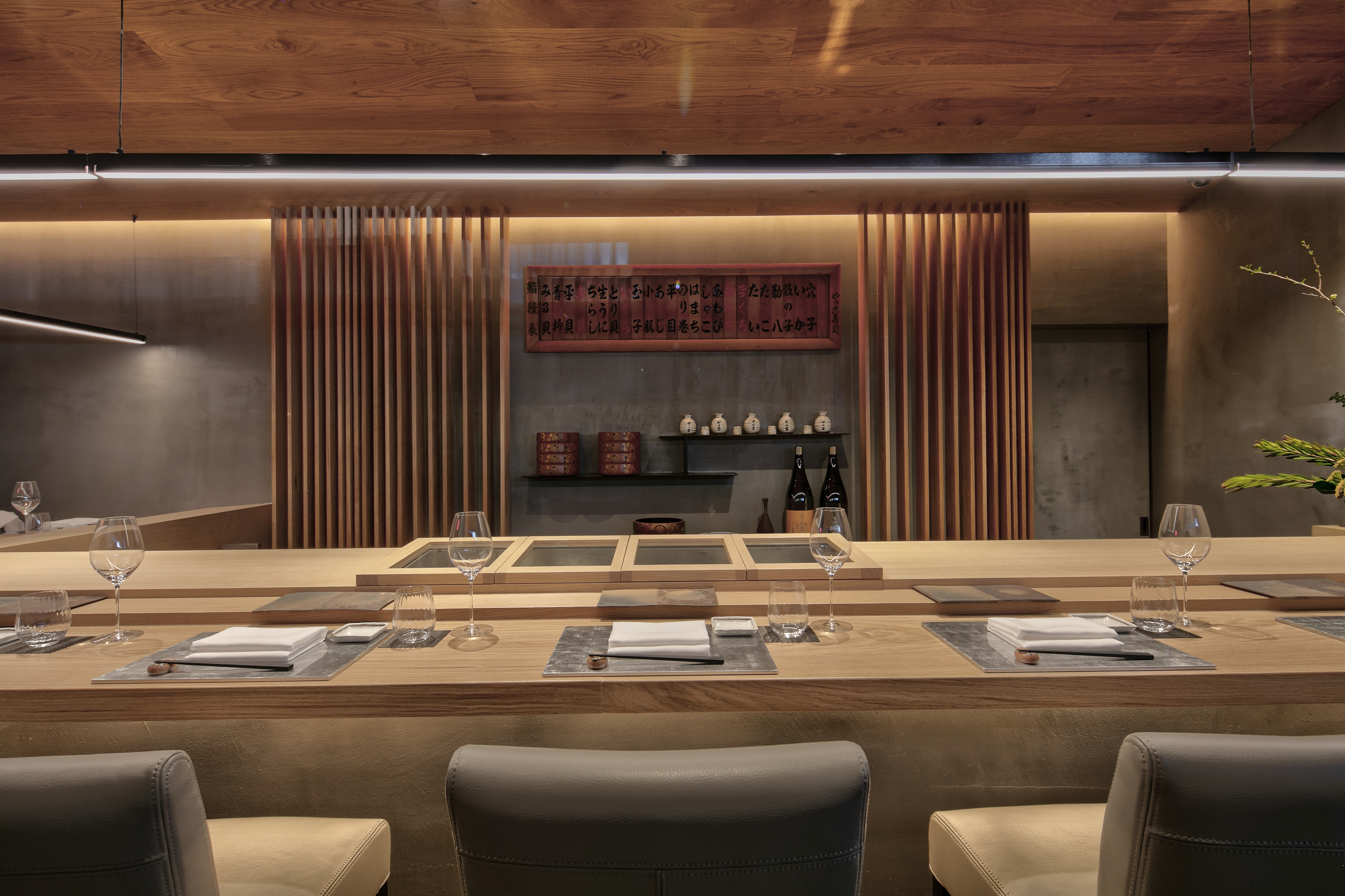 A head-on shot of the back of a sushi counter, with rows of brown chairs, light wood, and heirloom sake glasses on a shelf.