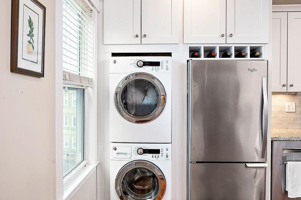 A closeup of a fridge next to a stacked washer-dryer, with a wine rack right above the fridge.