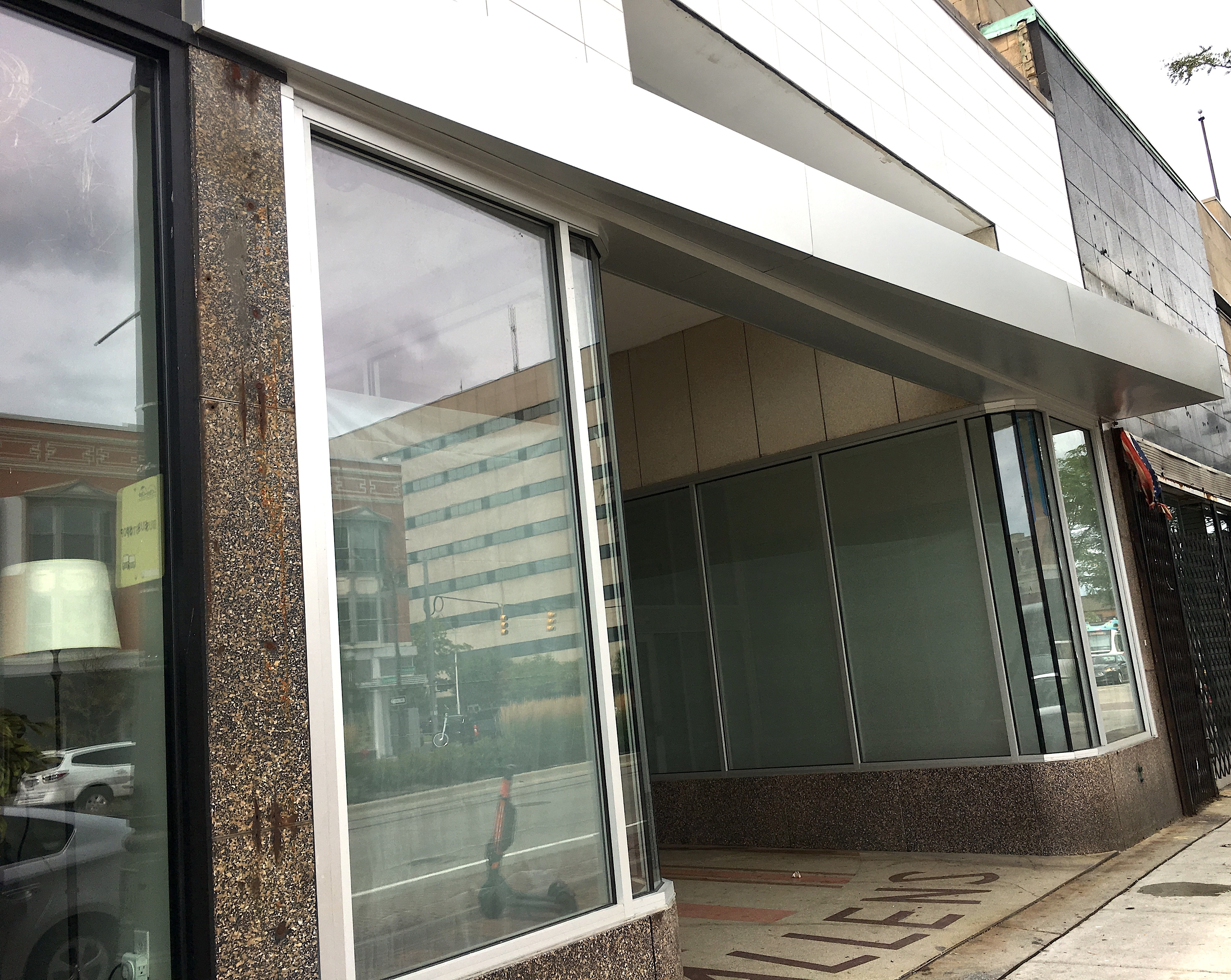 Large windows and a metallic angled panel hanging over the sidewalk on Woodward on a cloudy day.