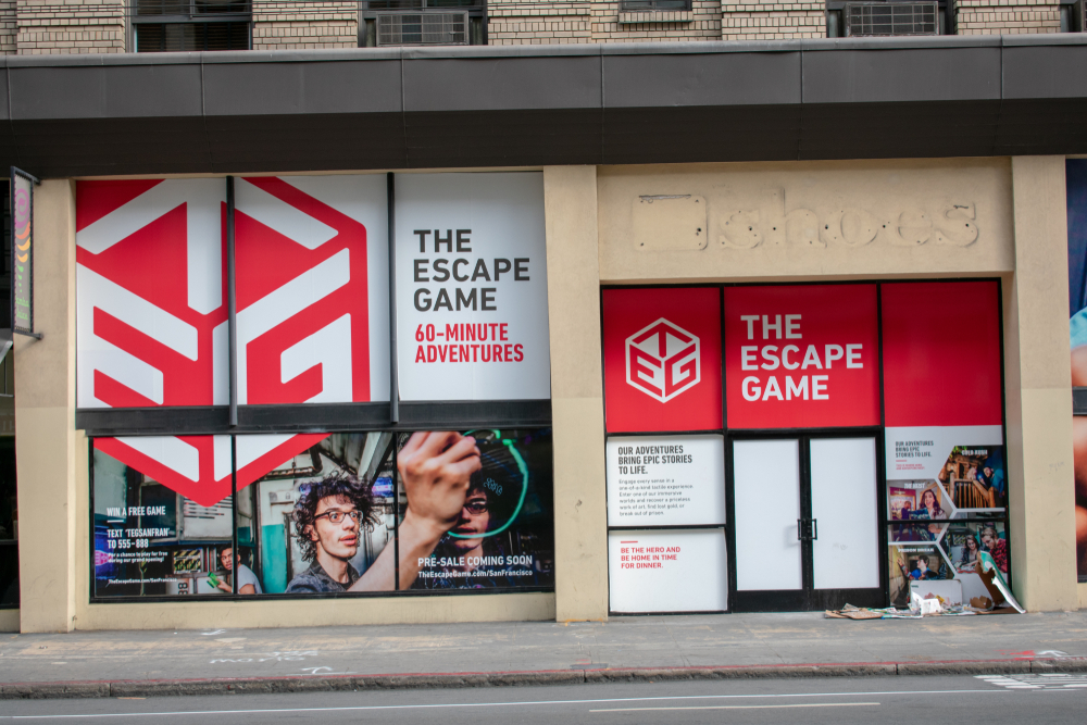 """An empty store with red and white signs reading """"escape game"""" plastered in the windows."""