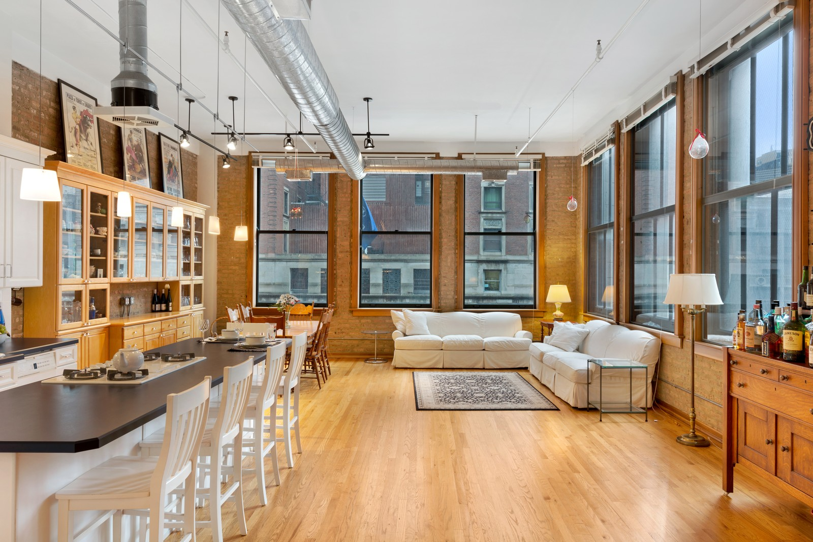 A living room with wood floors, high ceilings, and brick walls lined with windows. There is a pair of sofas and a kitchen with a breakfast bar island under pendant lights.