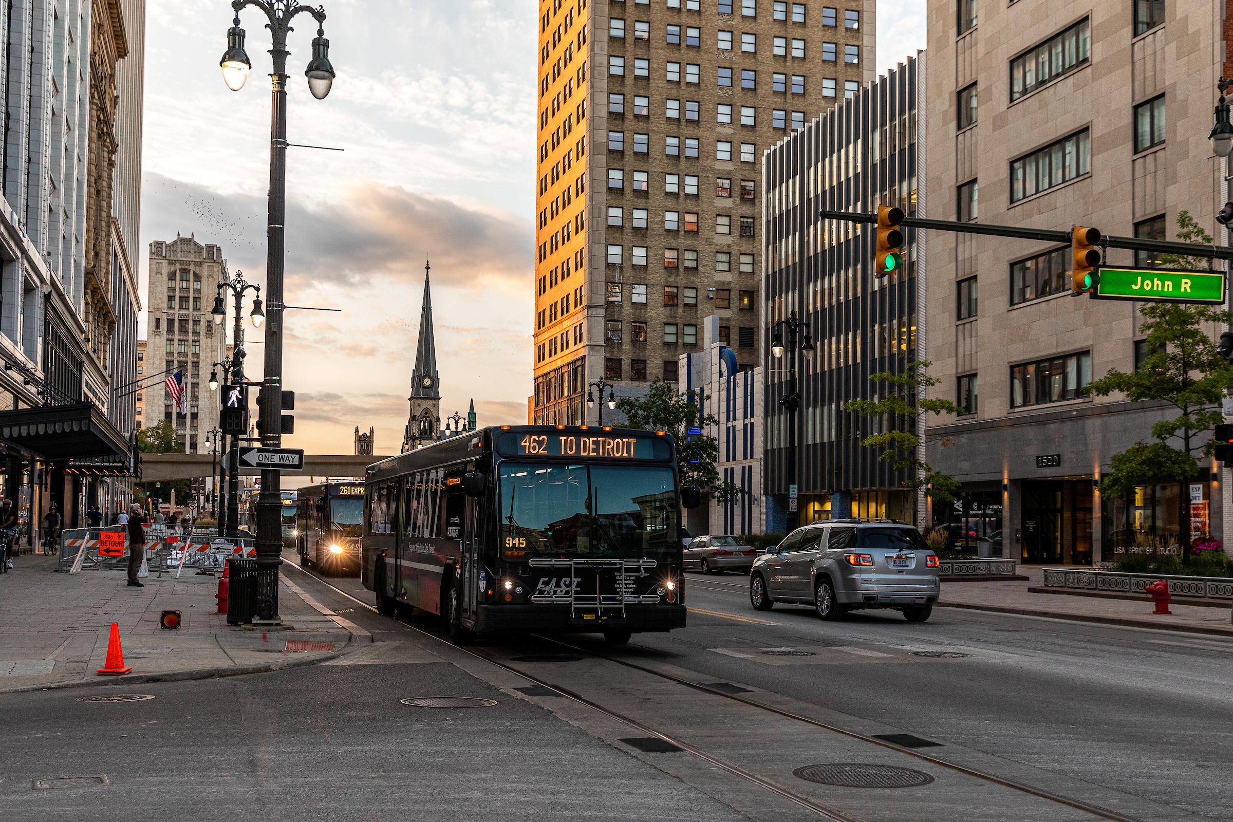 A black bus drives down a boulevard between tall buildings.