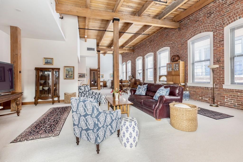 A cavernous and long living room with exposed bricks and beams and several large windows.