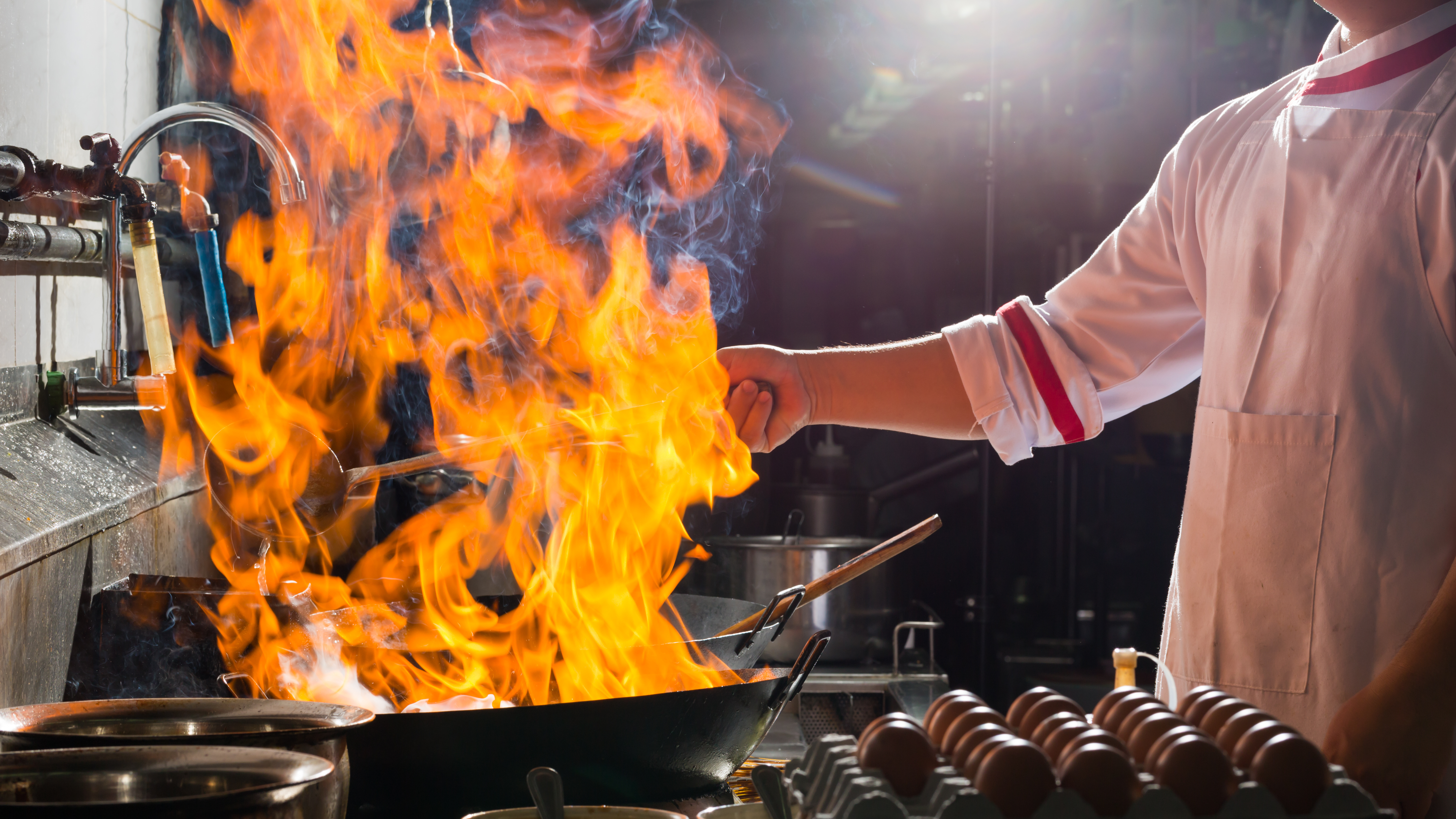 An iron pan on fire in a restaurant kitchen