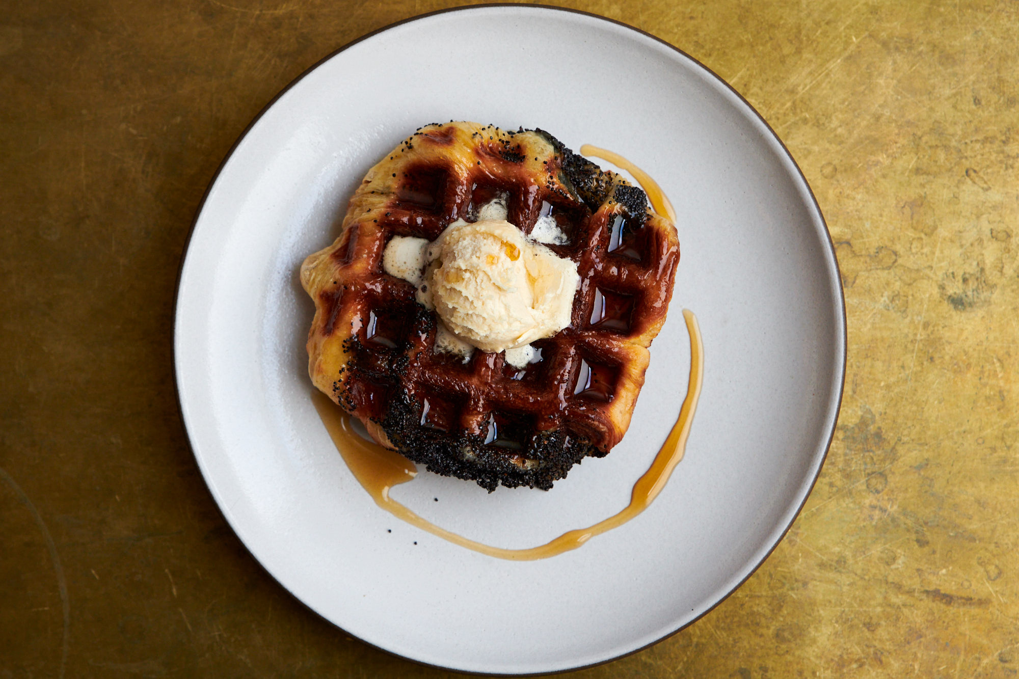 A unevenly shaped, leavened waffle sits on a white plate with a scoop of maple butter on top. A drizzle of maple syrup swipes around its exterior.
