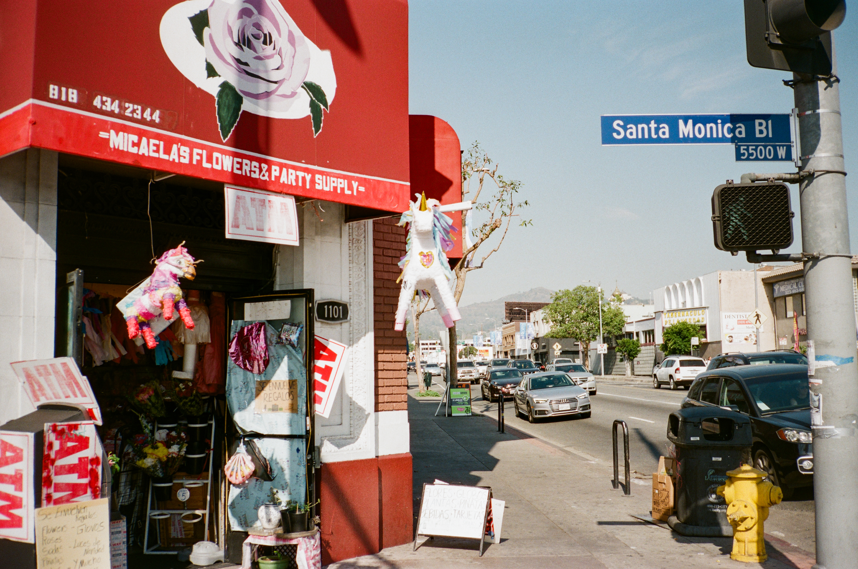A red awning with a pink rose on it, the outside of Micaela's Flowers & Party Supply, has two unicorn pinatas hanging. The shop is at the corner of Santa Monica Blvd.