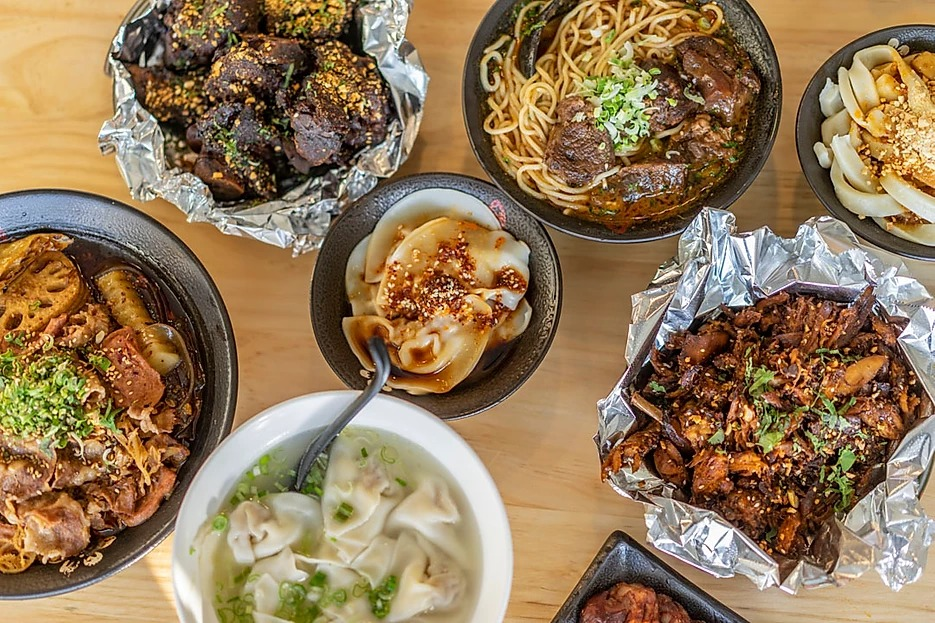 A variety of Sichuan dishes spread on a table.
