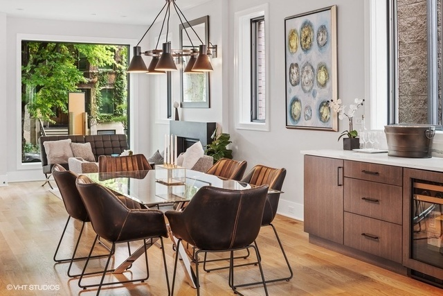 A dining room with a large table, countertop, and window.