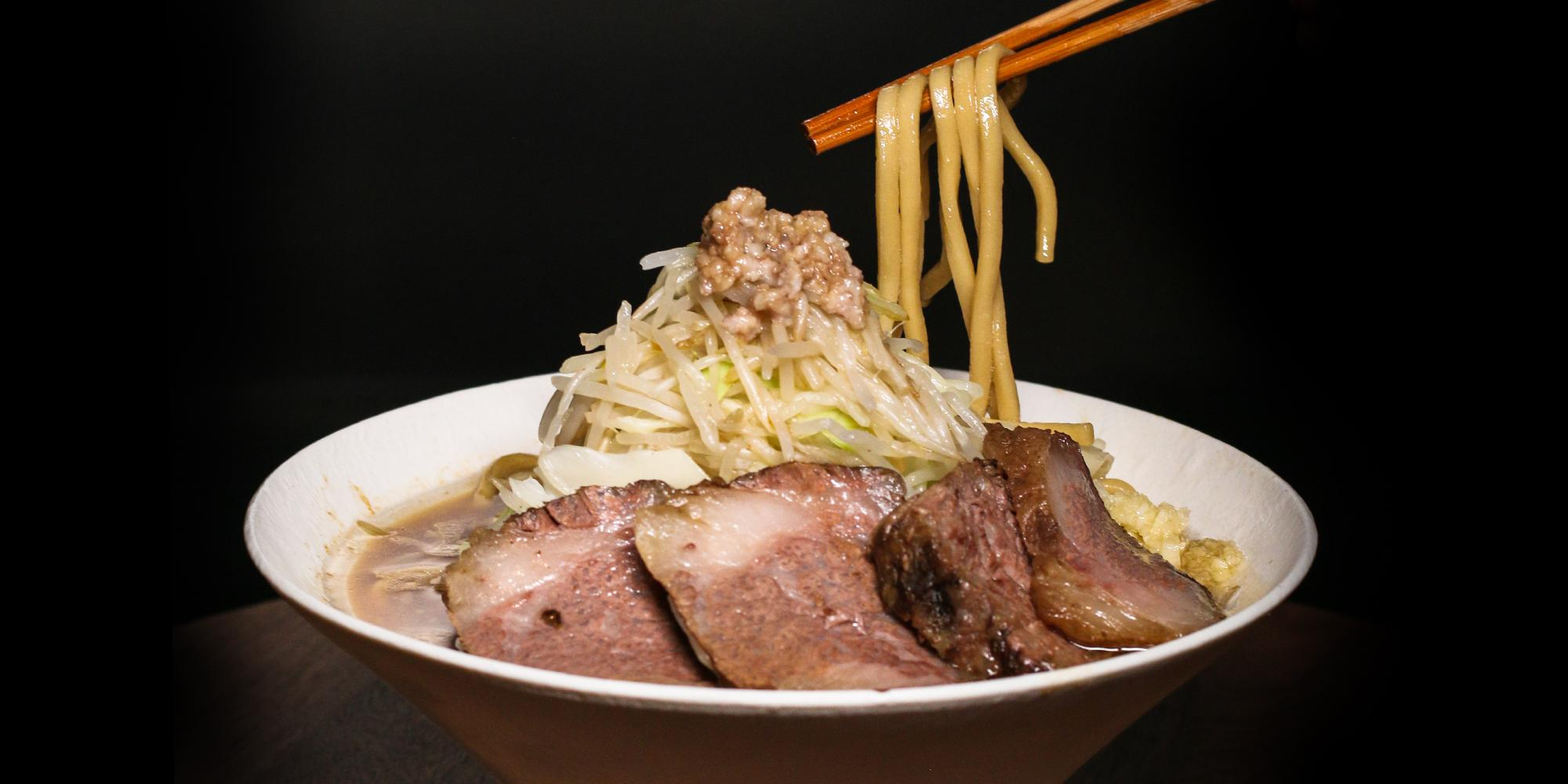 A bowl of wagyu jiro on a black background with chopsticks executing a noodle pull