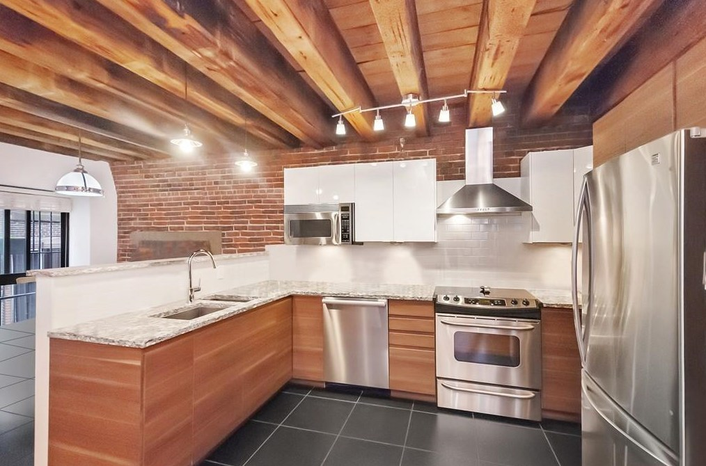An open kitchen with wood beams on the ceiling and an L-shaped counter.