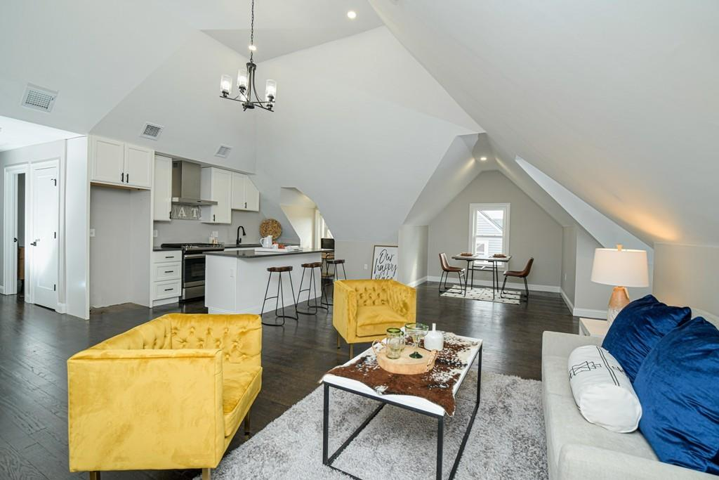 A living room with very high, peaked ceilings and furniture, and it's open to the kitchen and dining area.