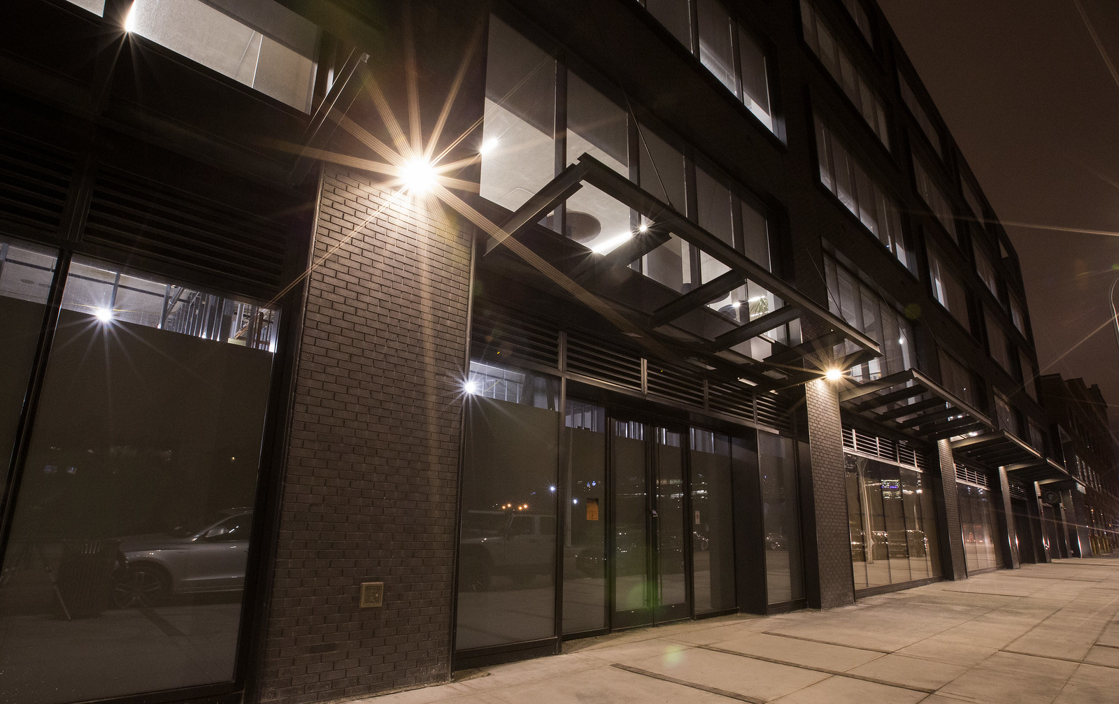 The modern exterior of an office building at night.
