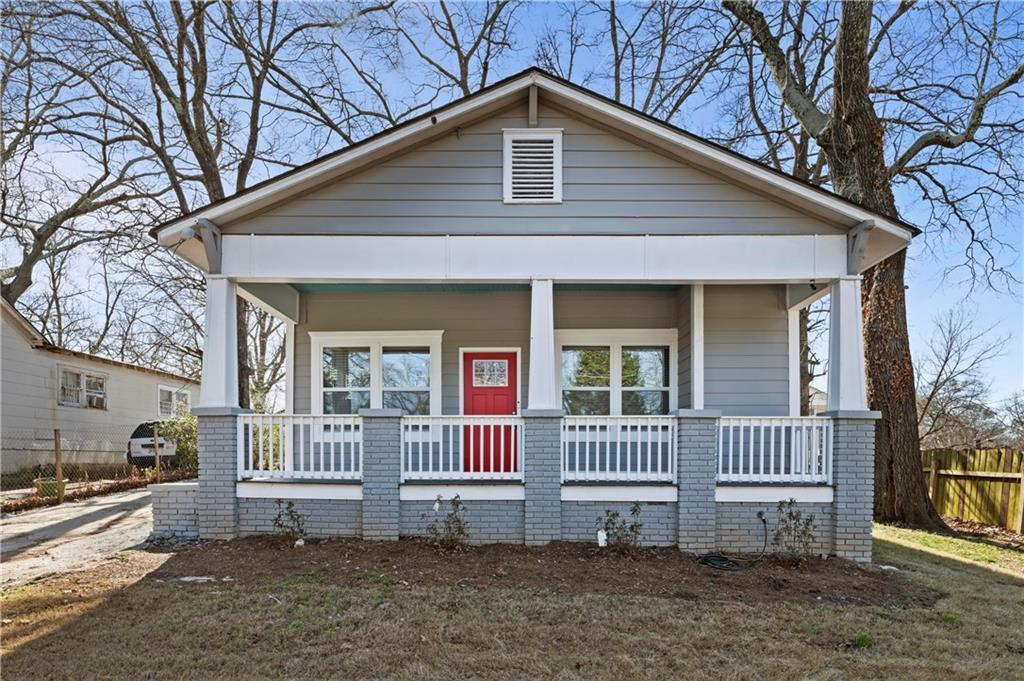 Gray bungalow with white trim and red front door.