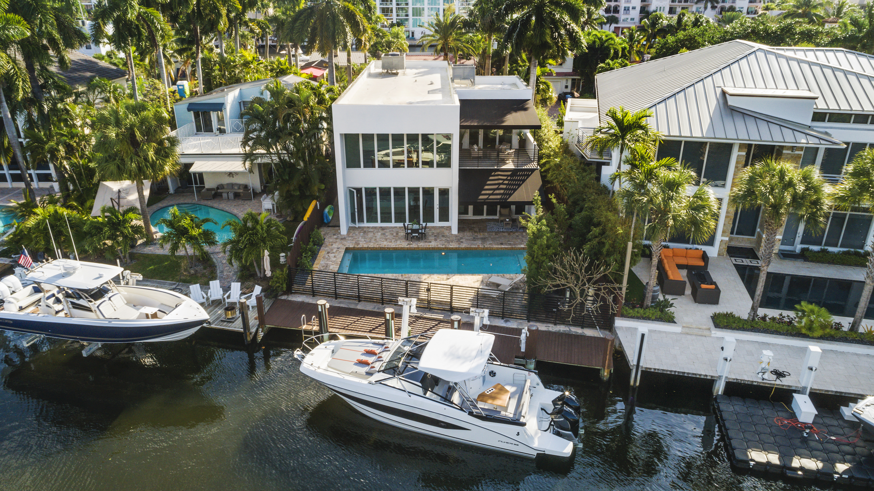 An aerial view of a waterfront all-white, boxy home. There's a pool and a boat in front.