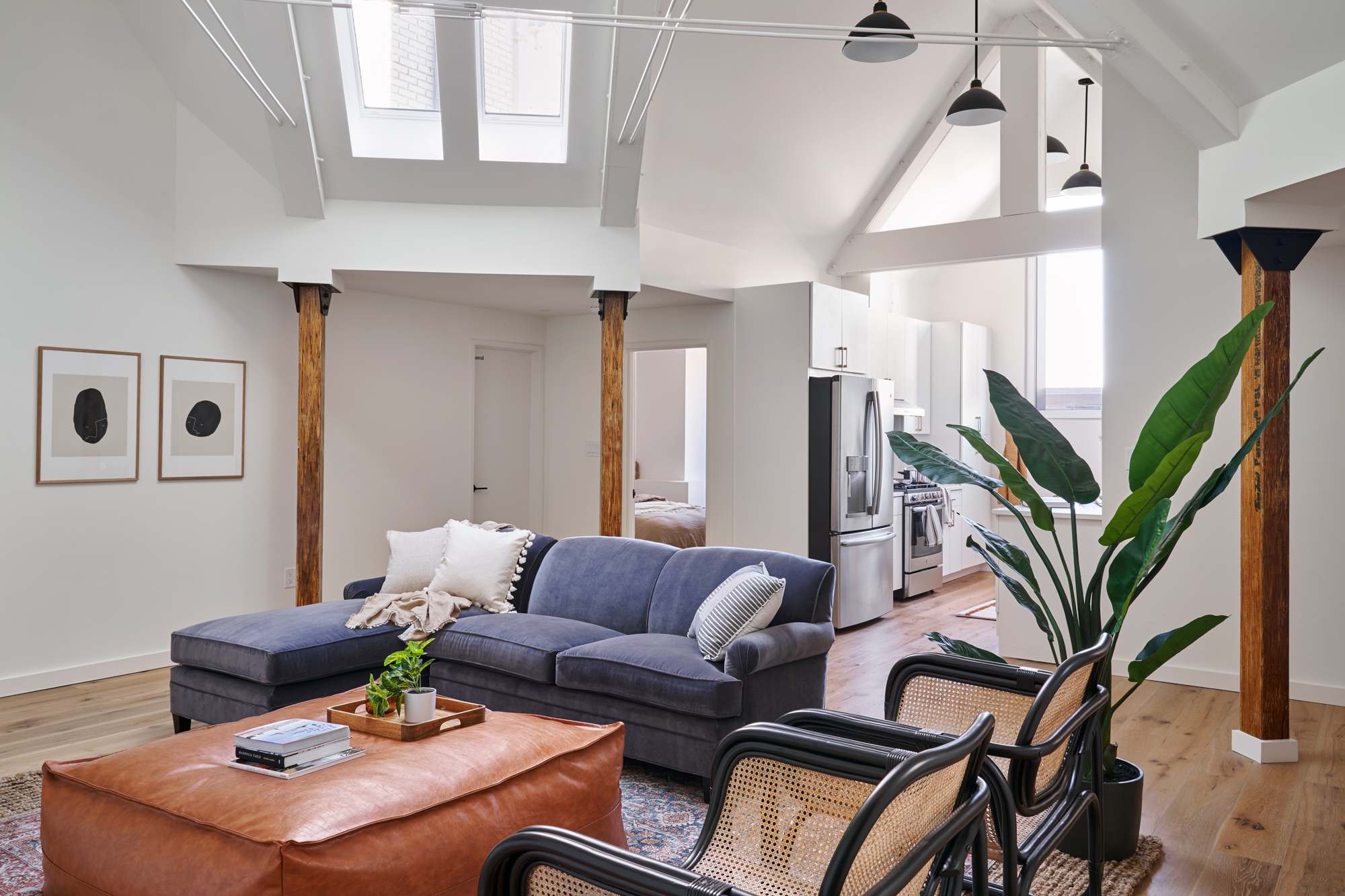 Living room with cathedral ceilings, exposed wooden beams, and a sectional sofa with square ottoman.