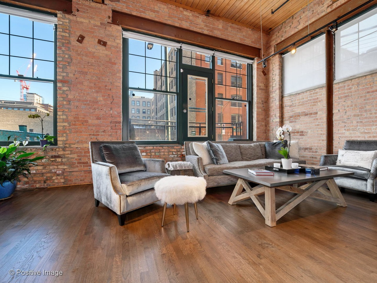 A lofted living room with brick walls and a sofa, chairs, and coffee table in front of oversized warehouse style windows.