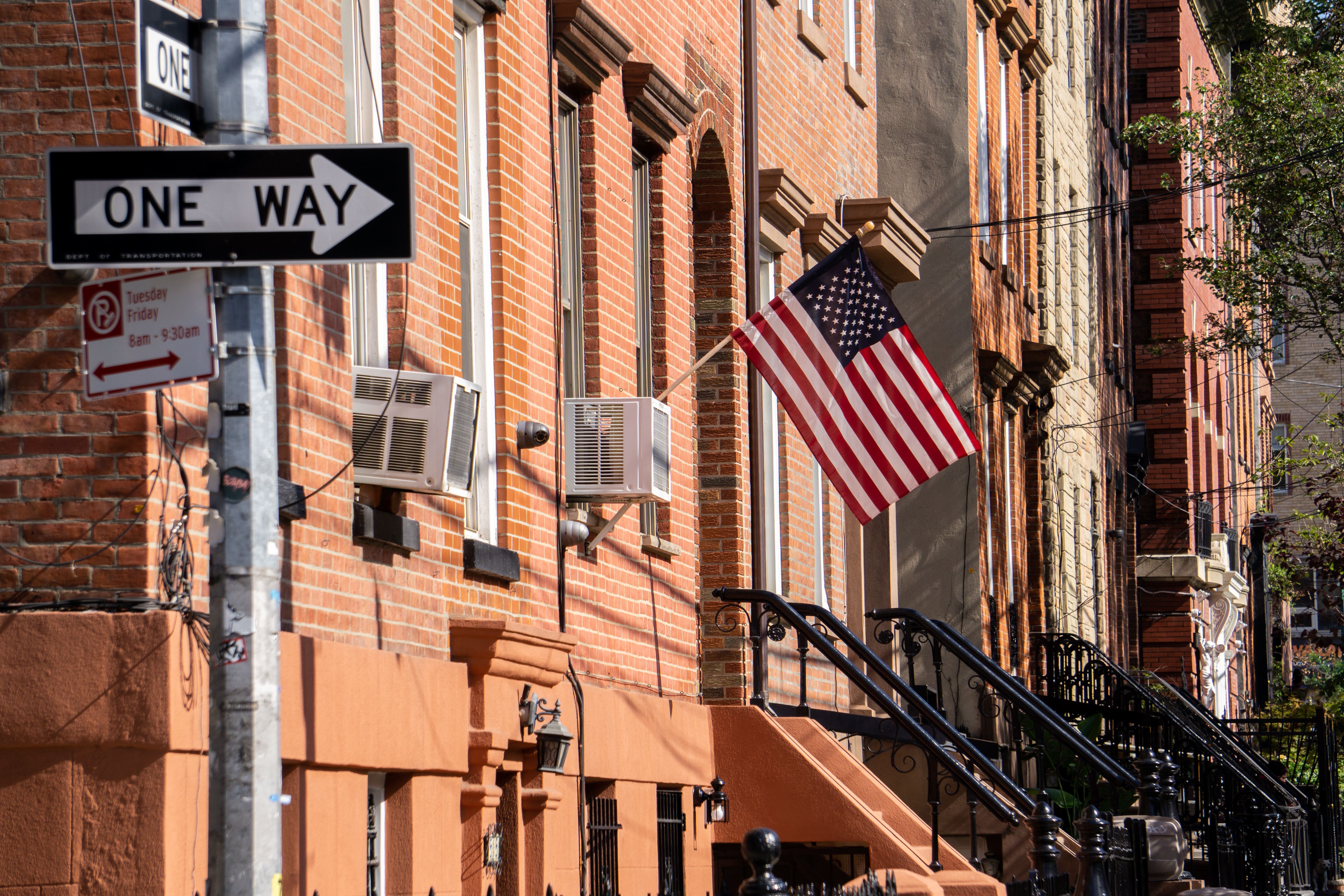 An American flag on a front porch is shown in front of row of brownstones on a New York street.
