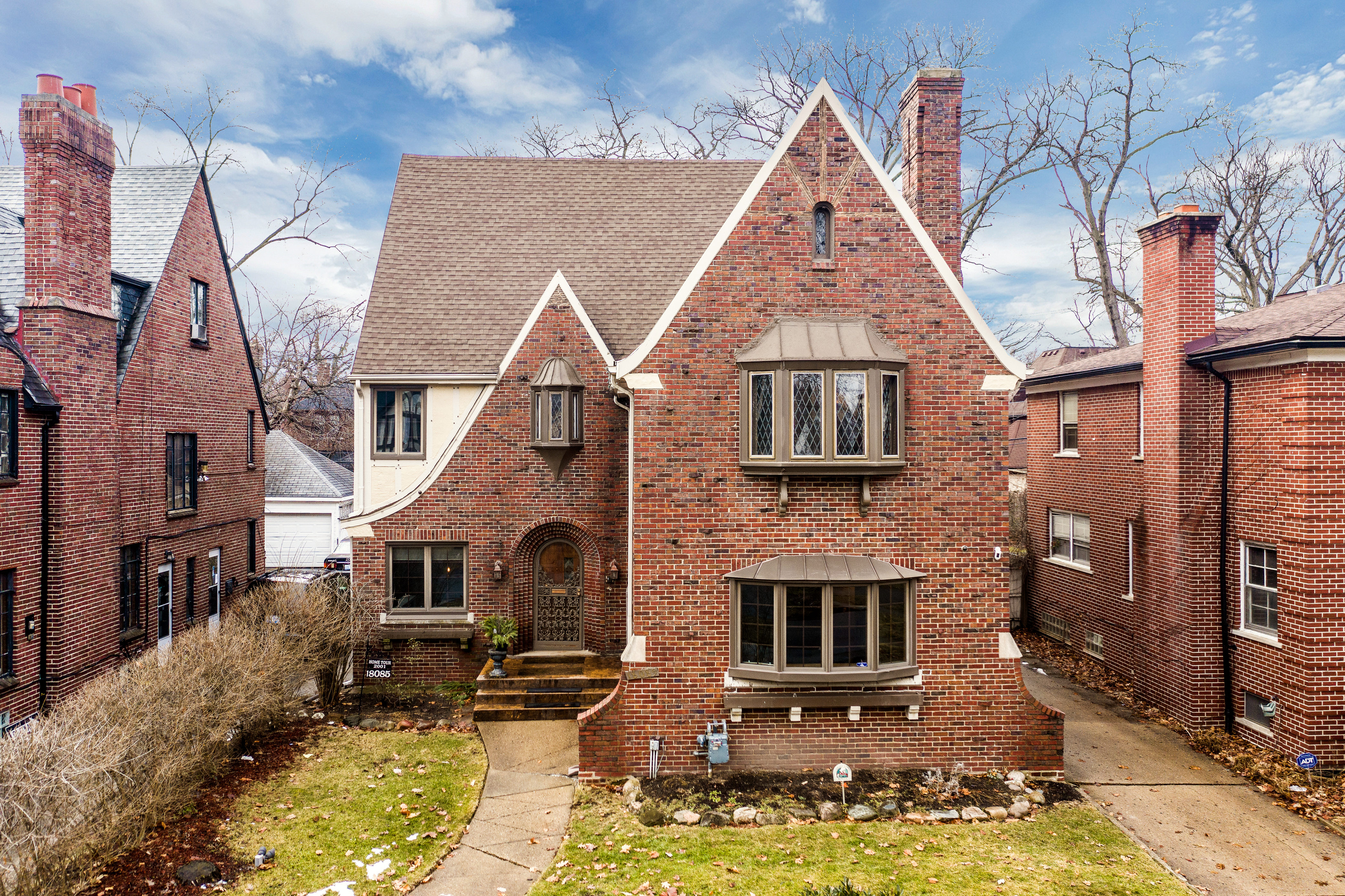 A brick home with multiple roof lines and leaded glass bay windows.